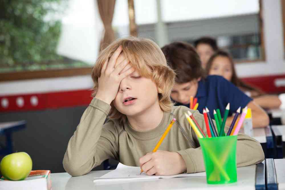 bored and tired young boy in school