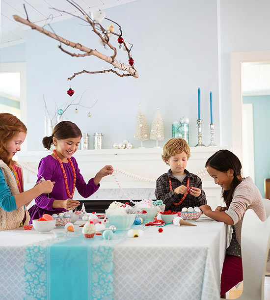 Kids around ornament crafting table with branch overhead