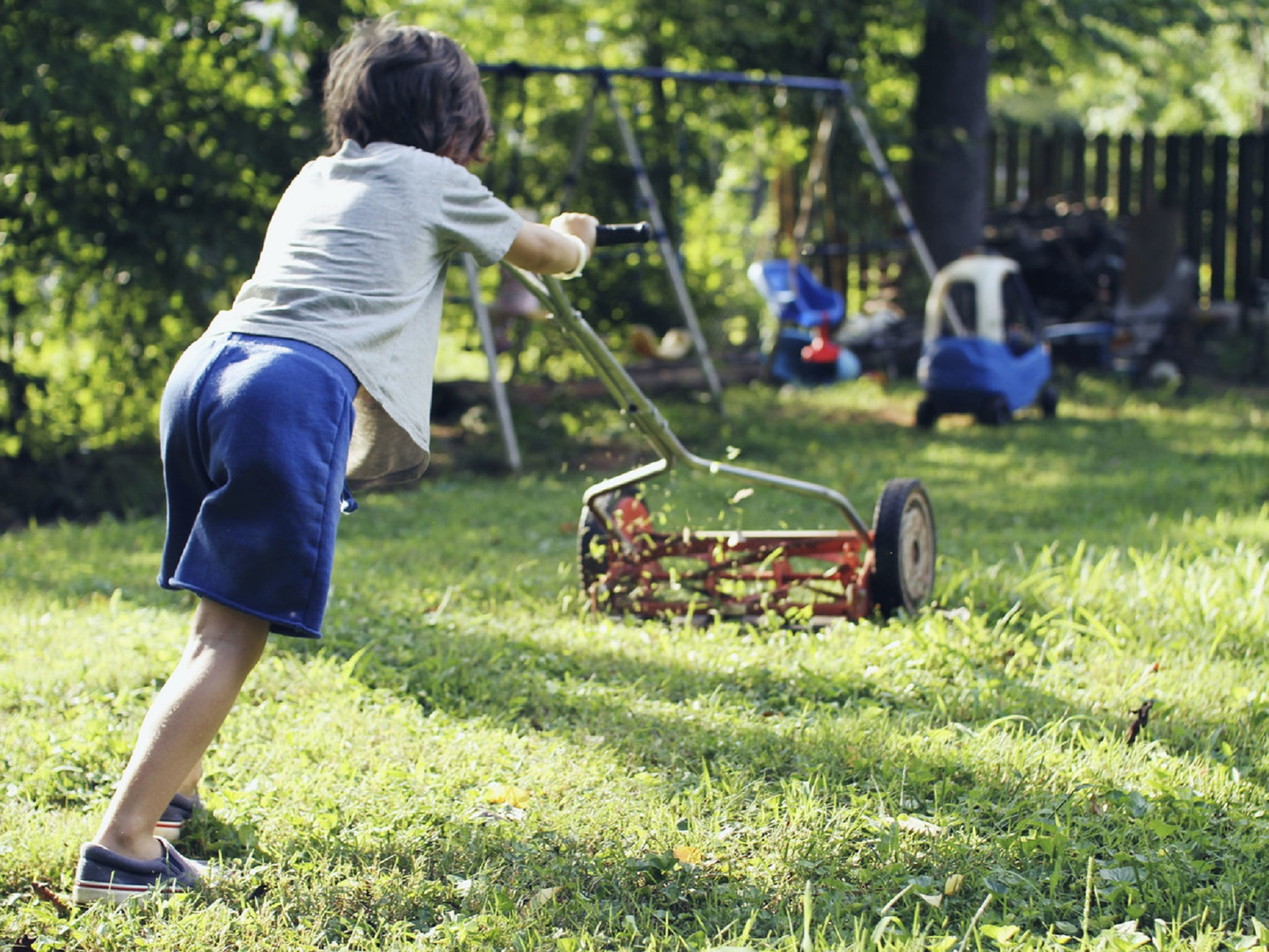 Blue Shorts Boy Mowing Lawn In Yard