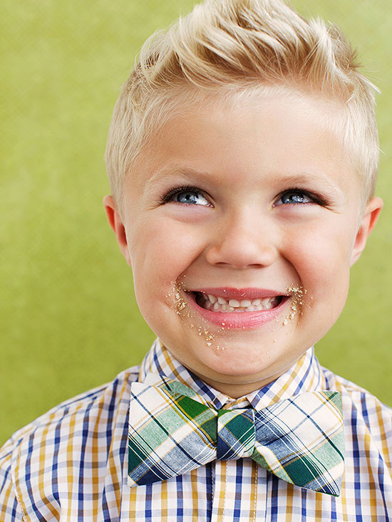 Smiling boy in bowtie with cookie crumbs on face