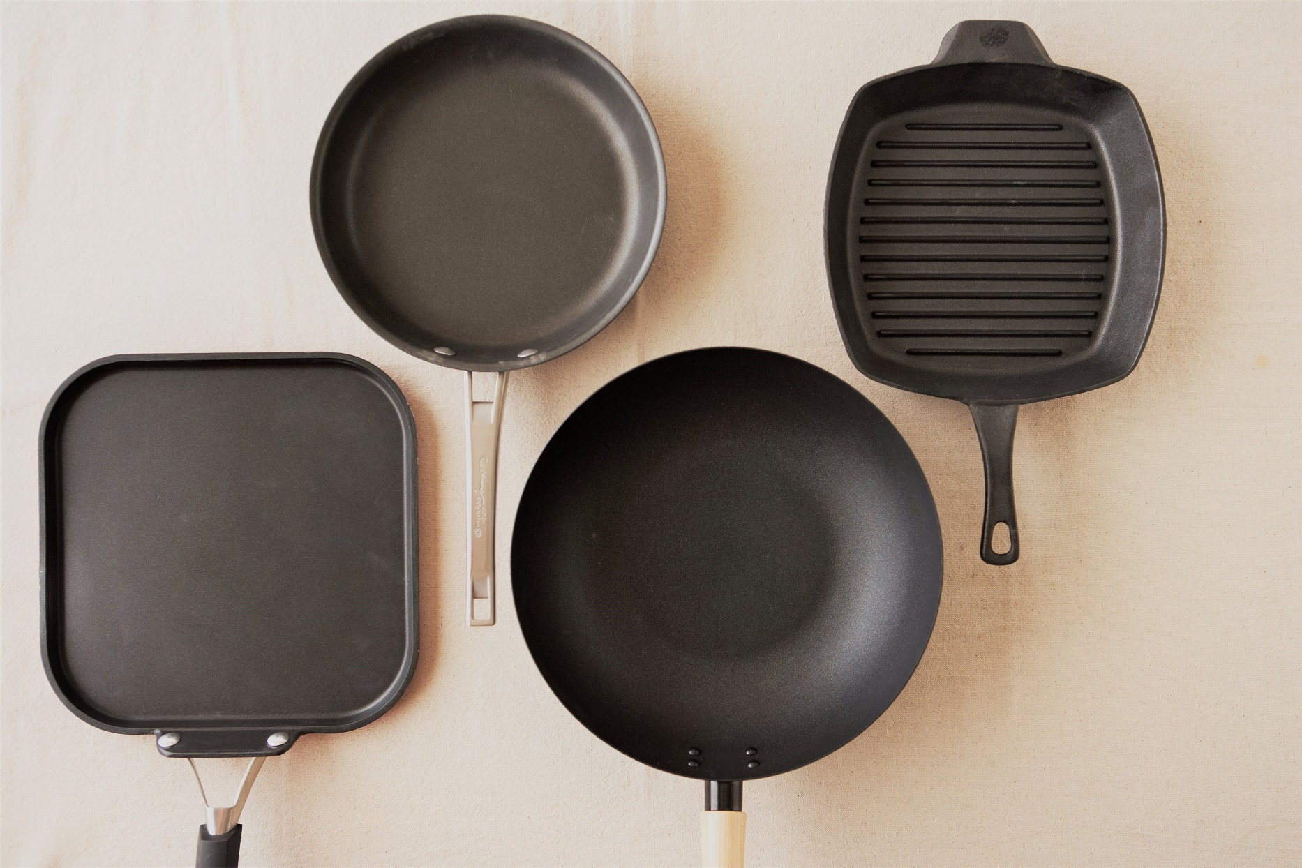 Four Frying Pans On Canvas Background