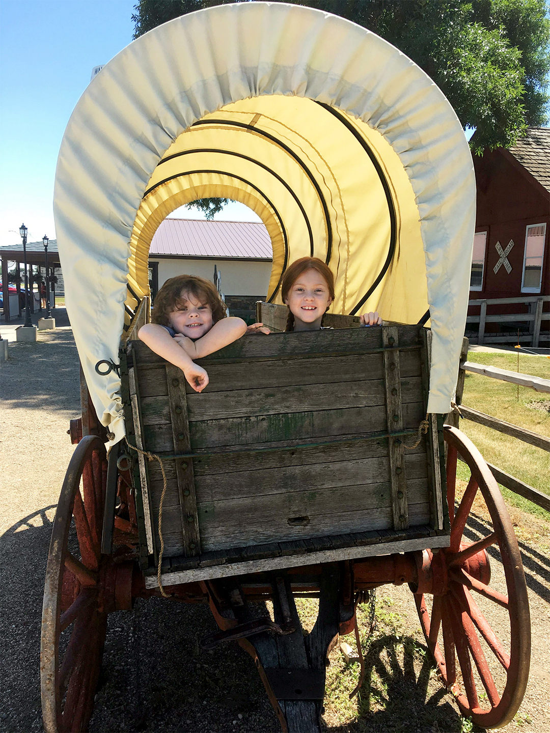 children sitting in a colonial covered wagon