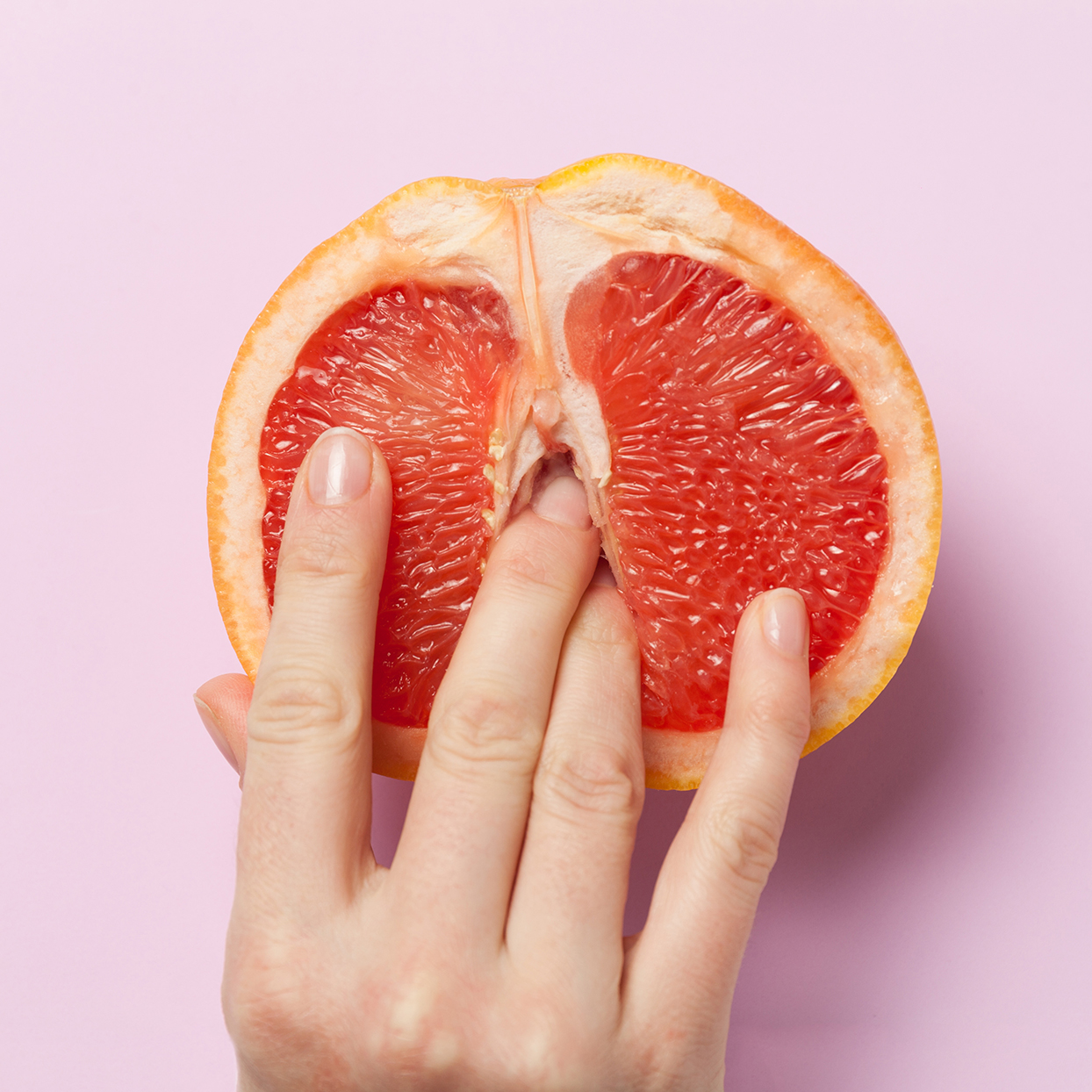 Female Fingers In Grapefruit Half