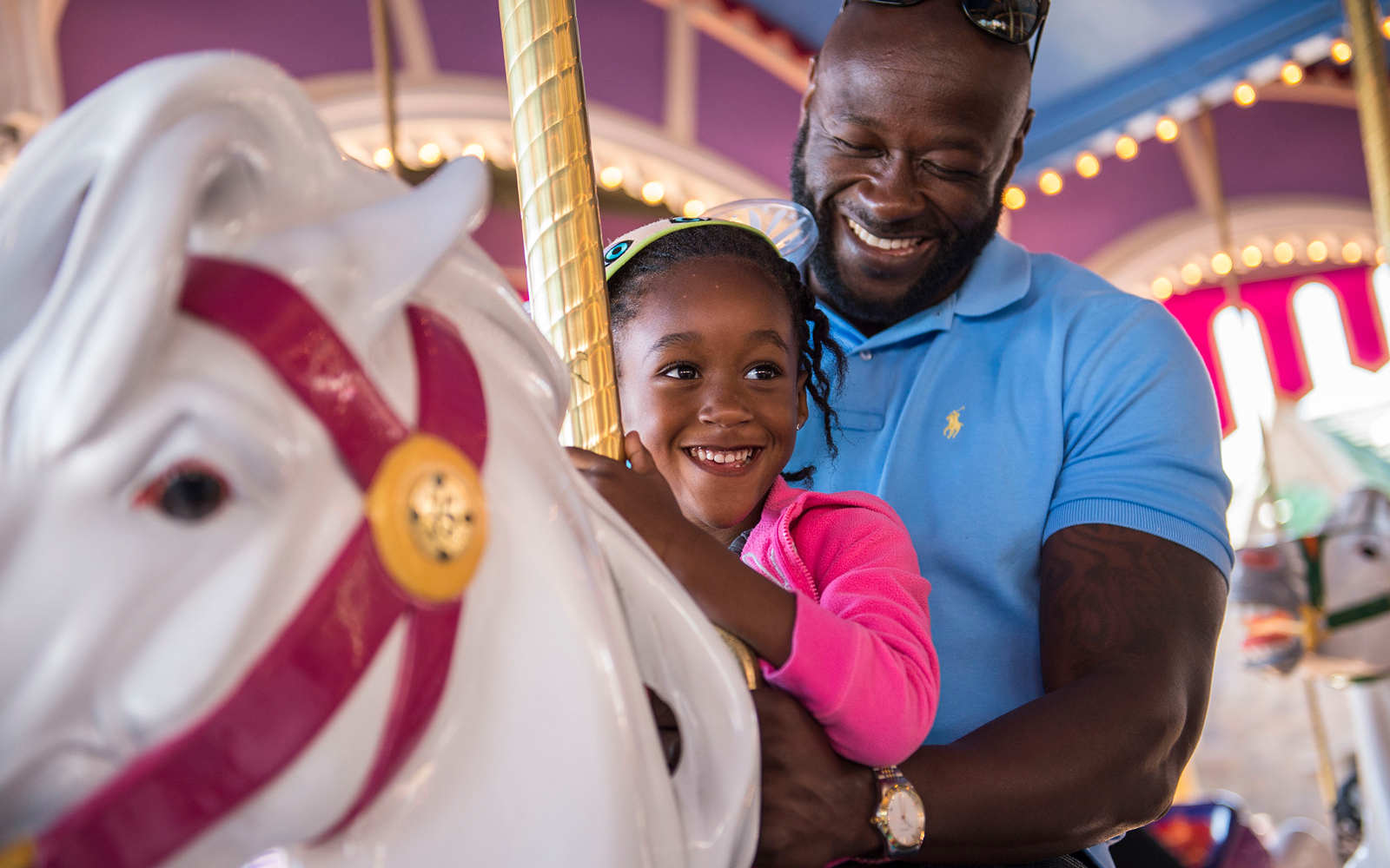 Black Father and Daughter on the Prince Charming Regal Carrousel in Disney World