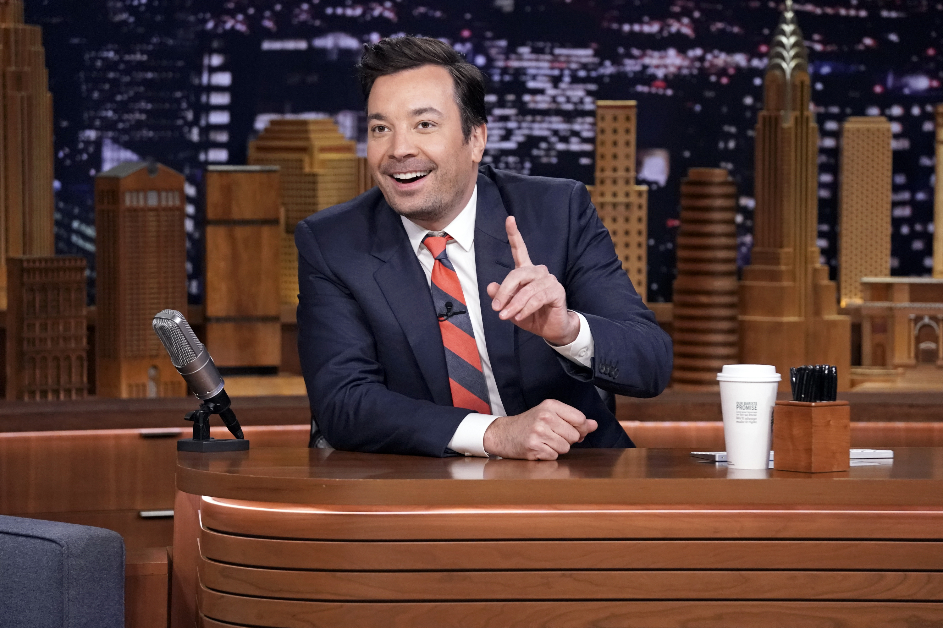 Jimmy Fallon Sitting at his Desk Pointing Up on The Tonight Show Starring Jimmy Fallon