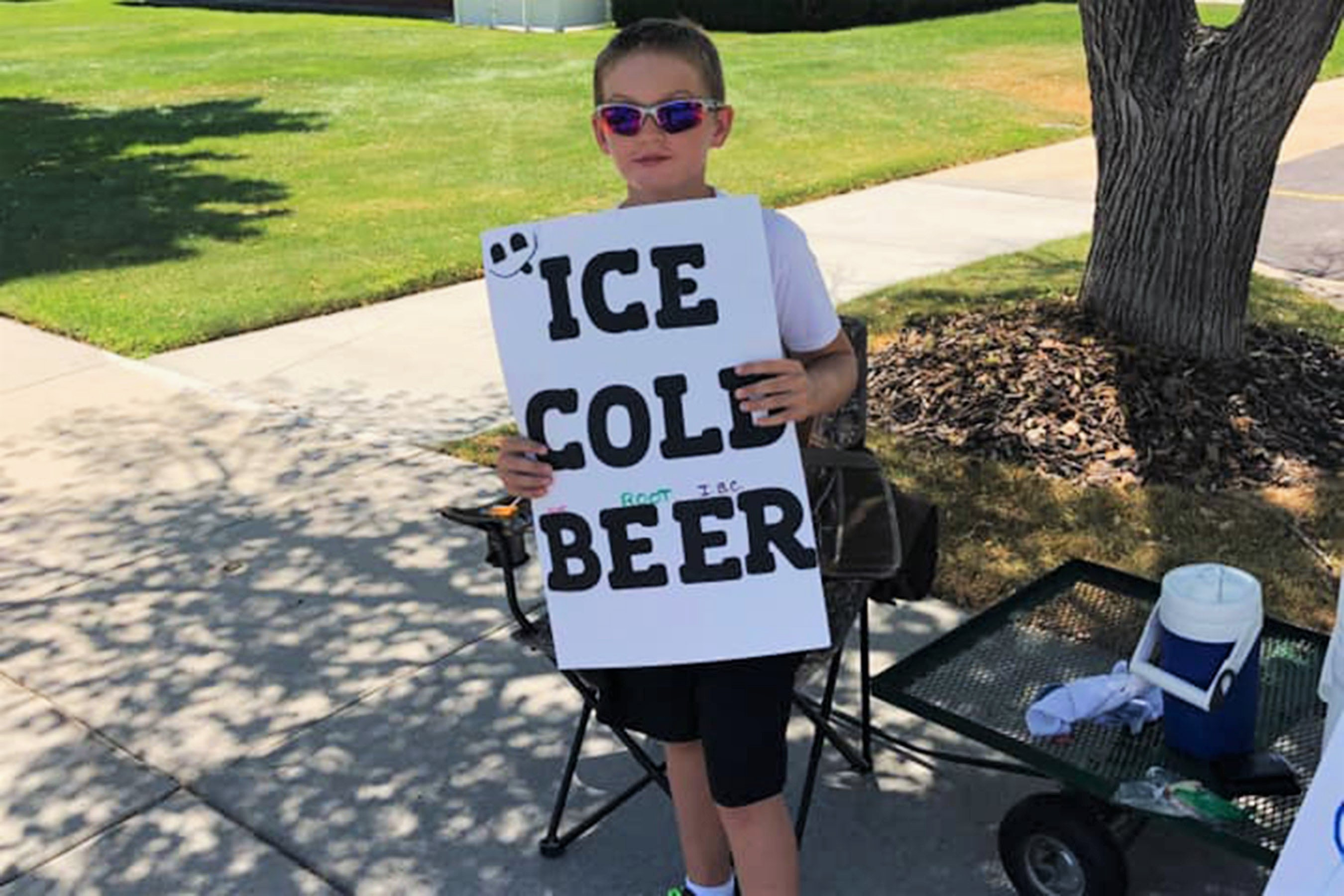 Utah boy selling root beer holding sign for ice cold beer