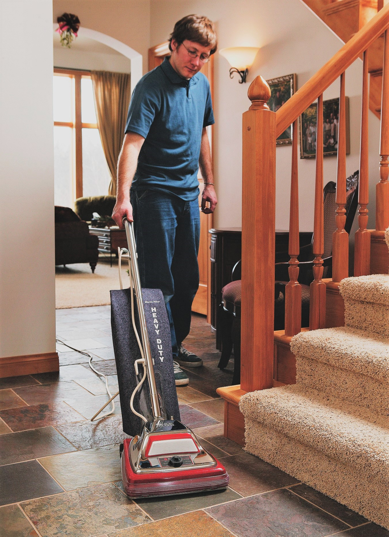 Man Vacuuming Near Staircase