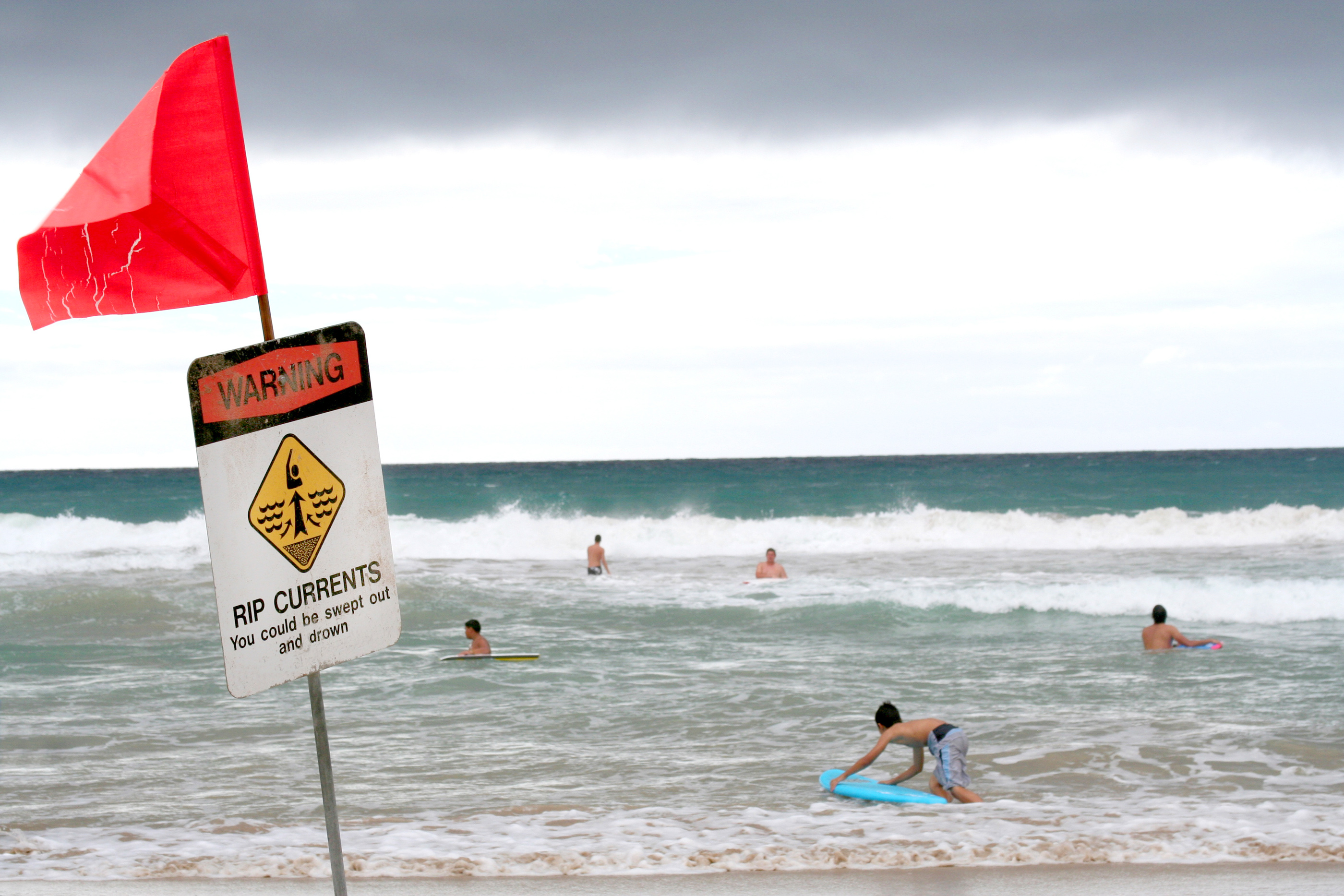 kids playing in the ocean with a rip current warning sign