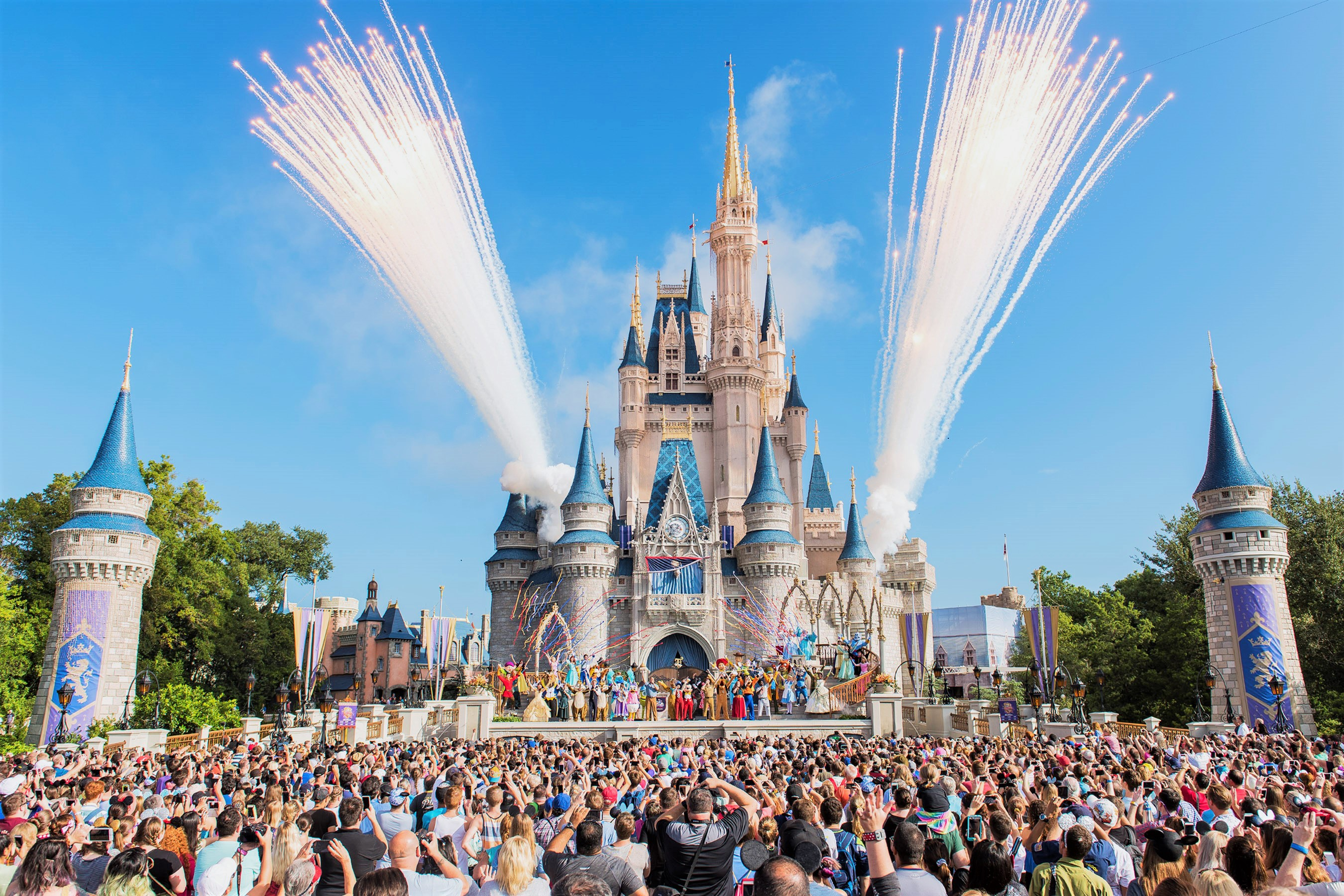 Disneyland Castle with Fireworks and Large Crowd During the Day
