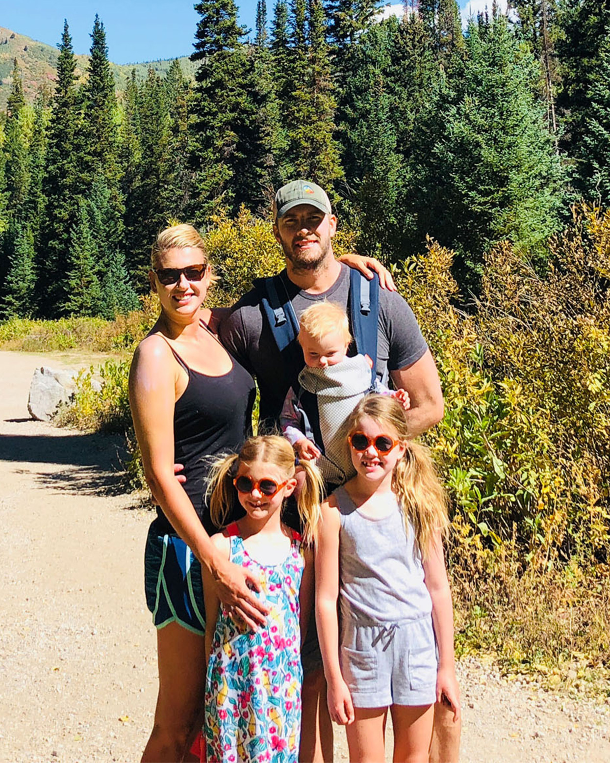 husband wife and three daughters on hiking trail