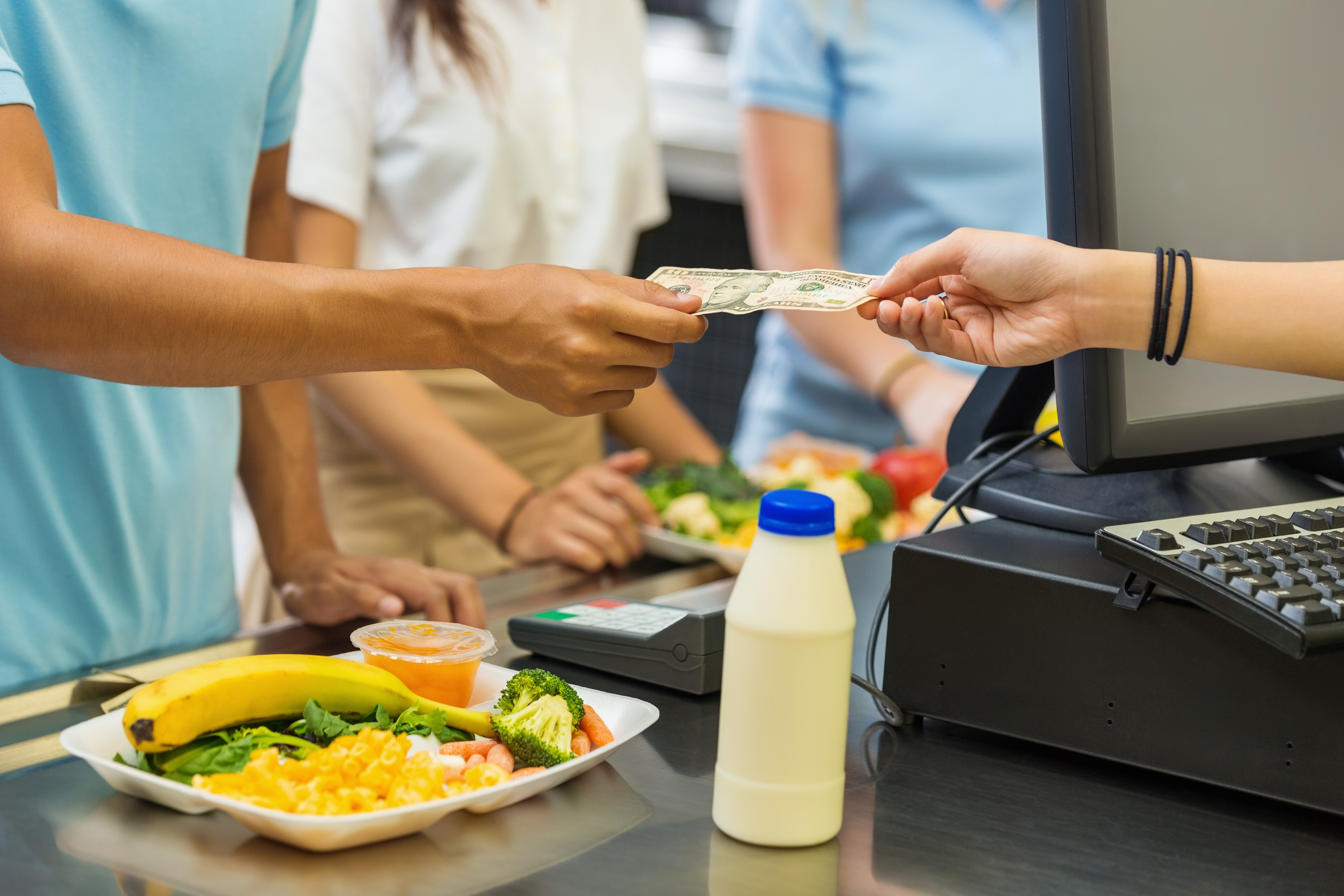Student paying for school lunch with cash in cafeteria at the register