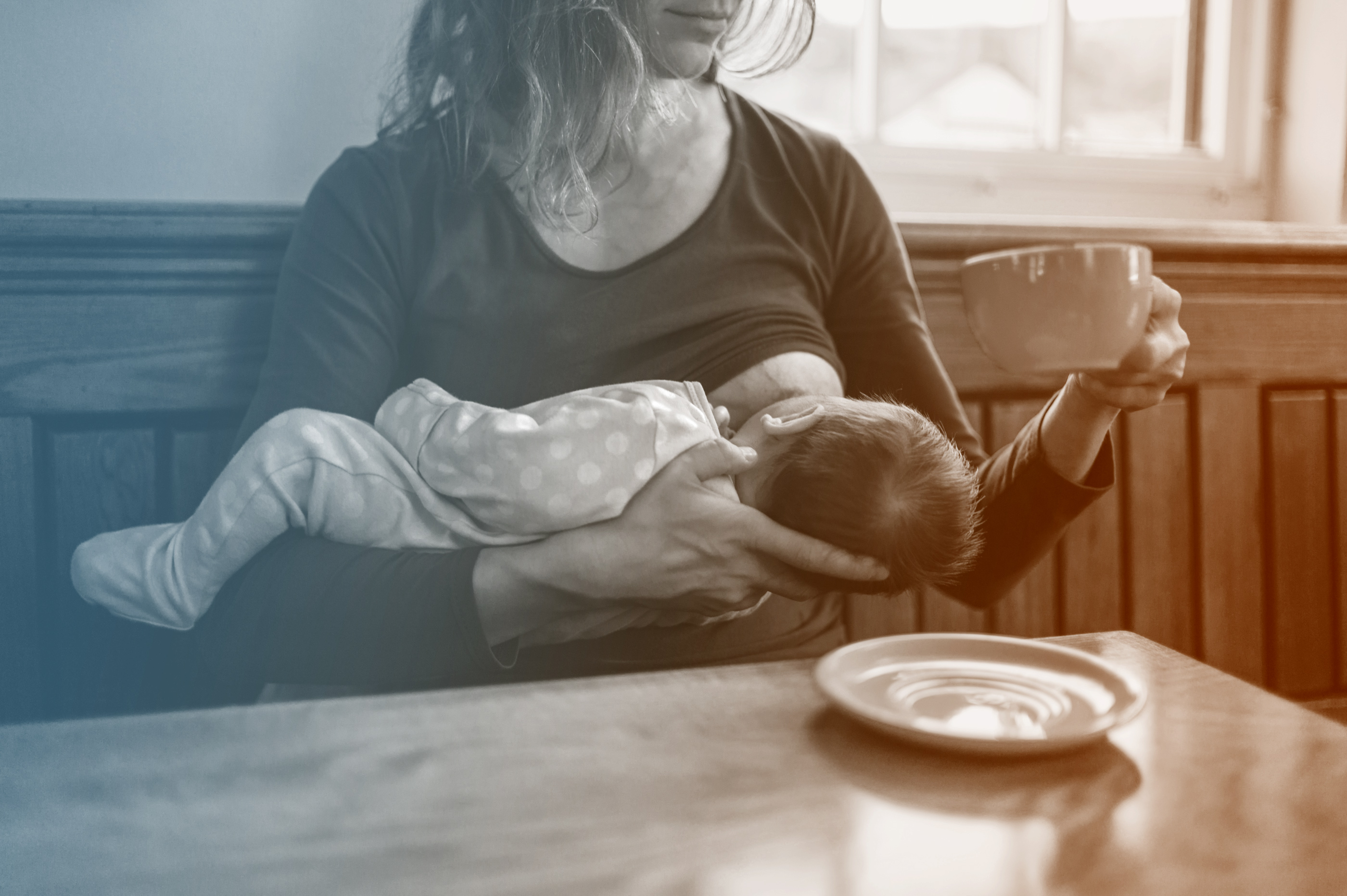 woman breastfeeding and having cup of coffee