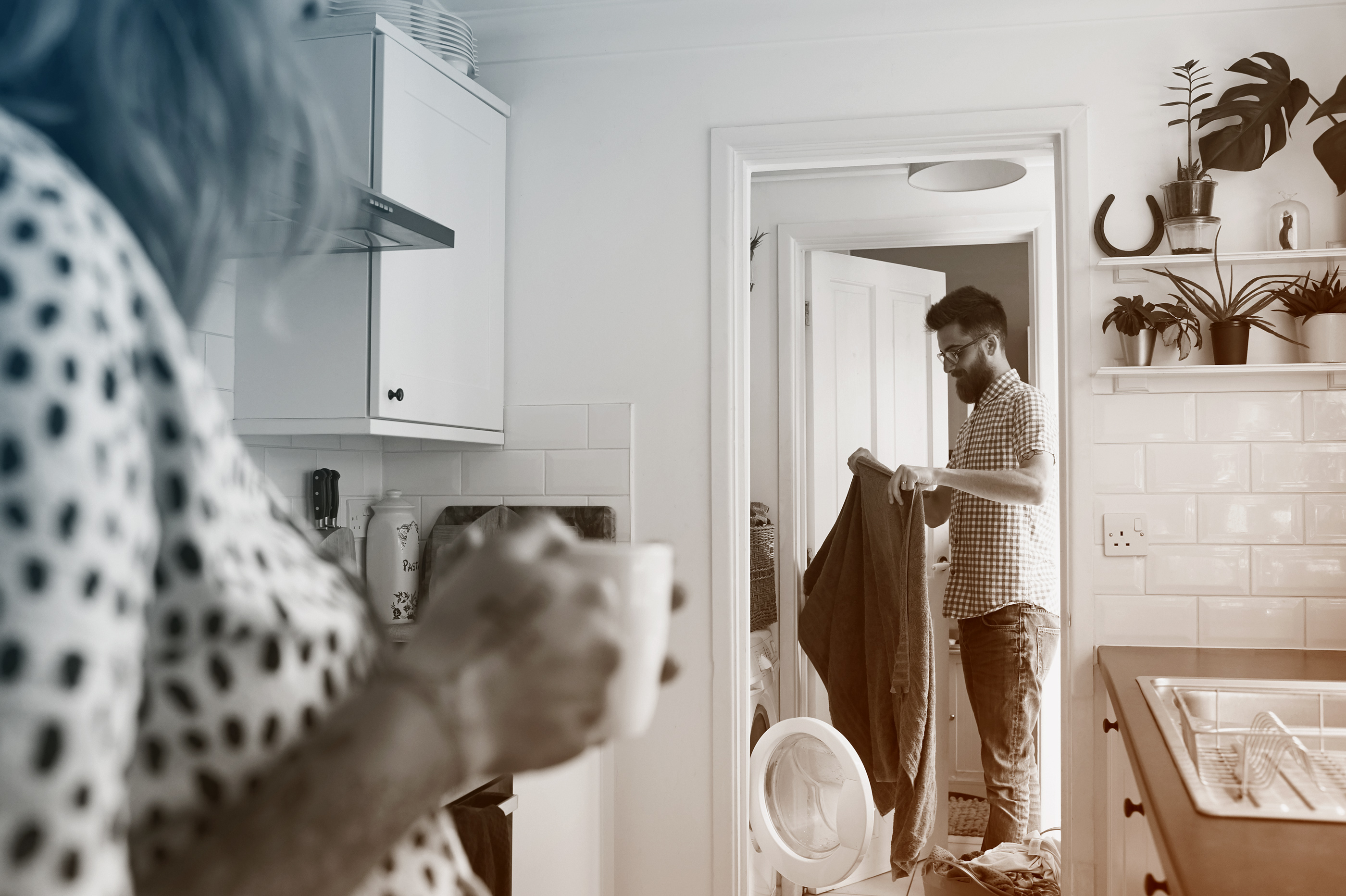 woman watching husband take laundry out of dryer