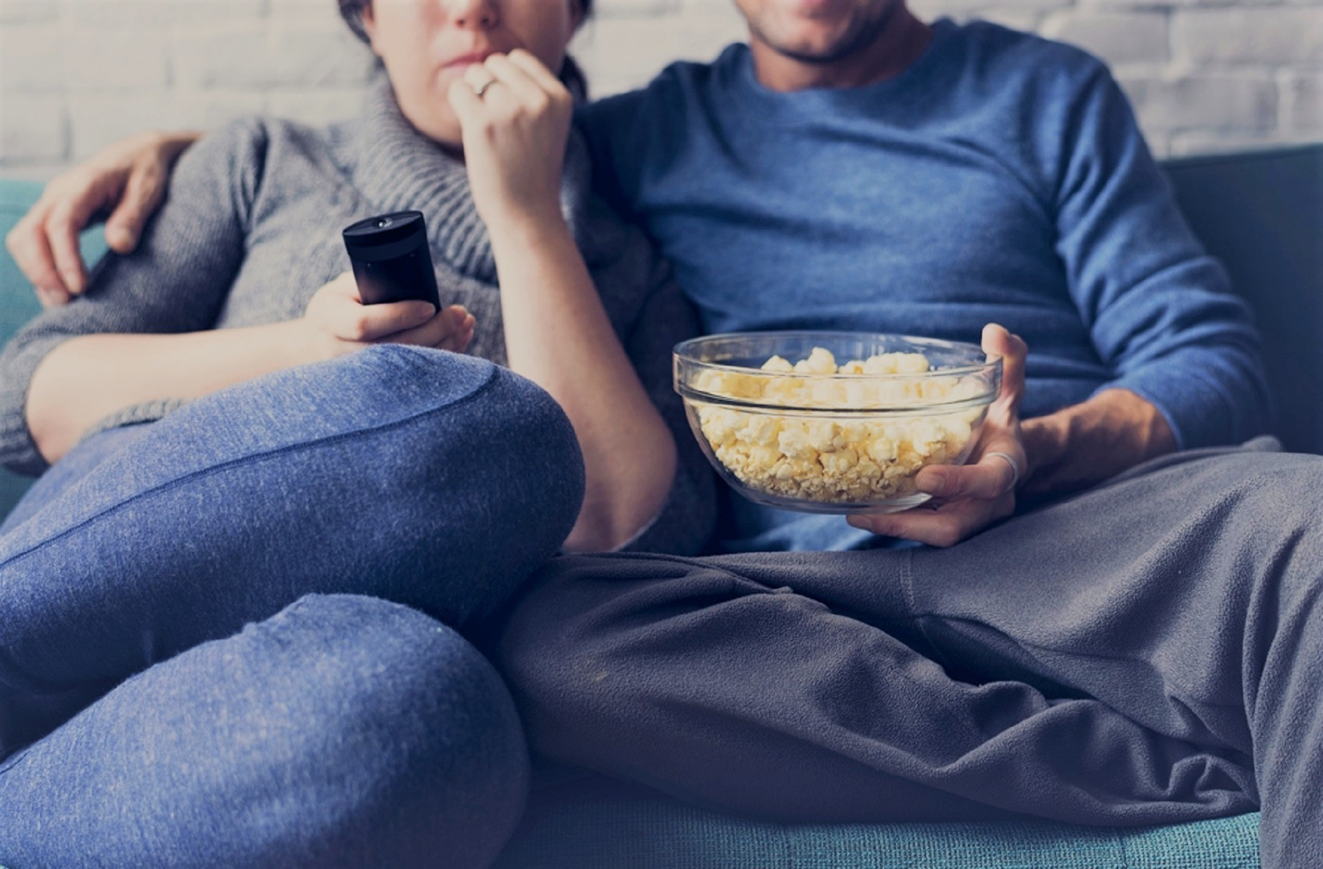 Couple Holding TV Remote and Bowl of Popcorn