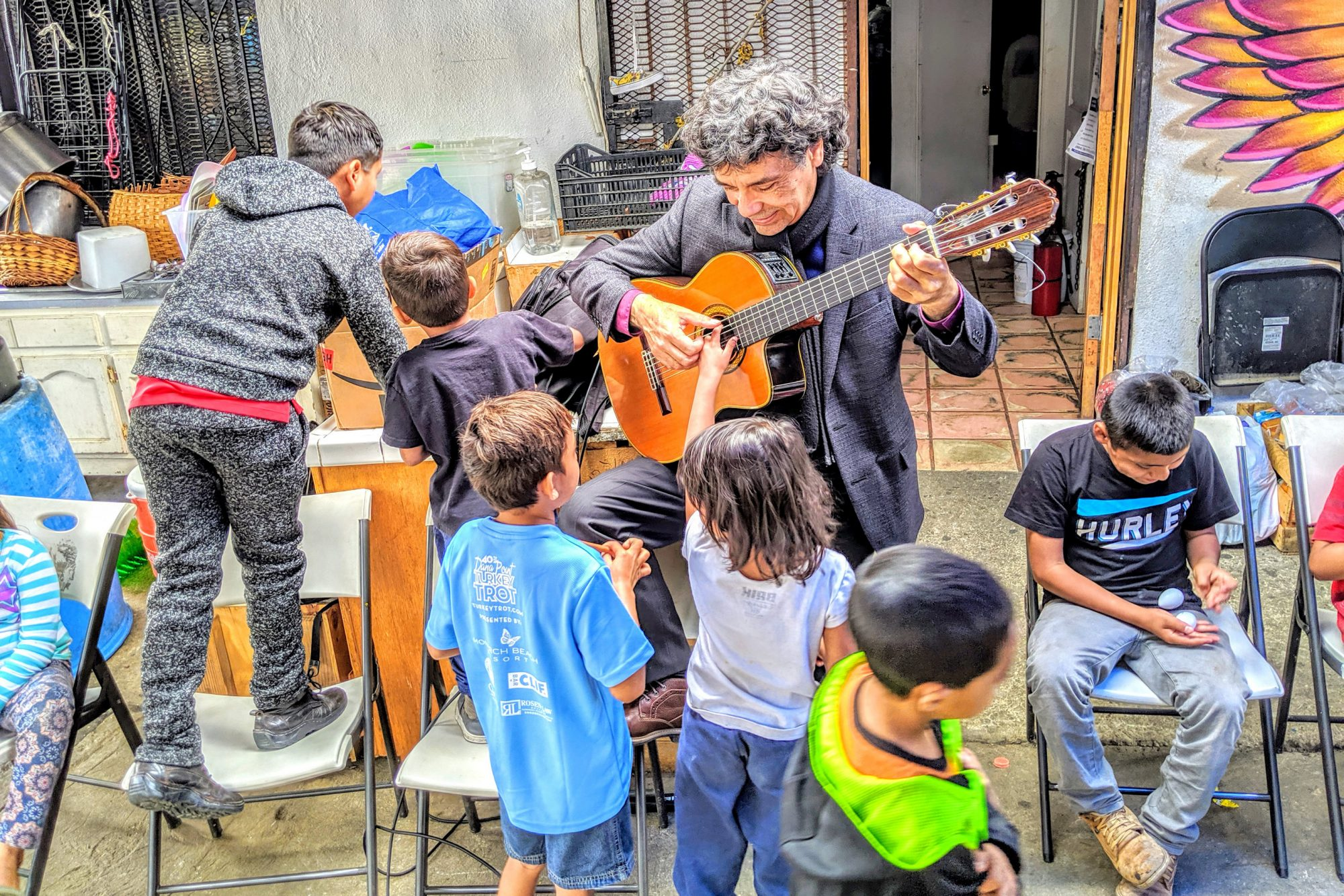 Man playing a guitar for children at the border