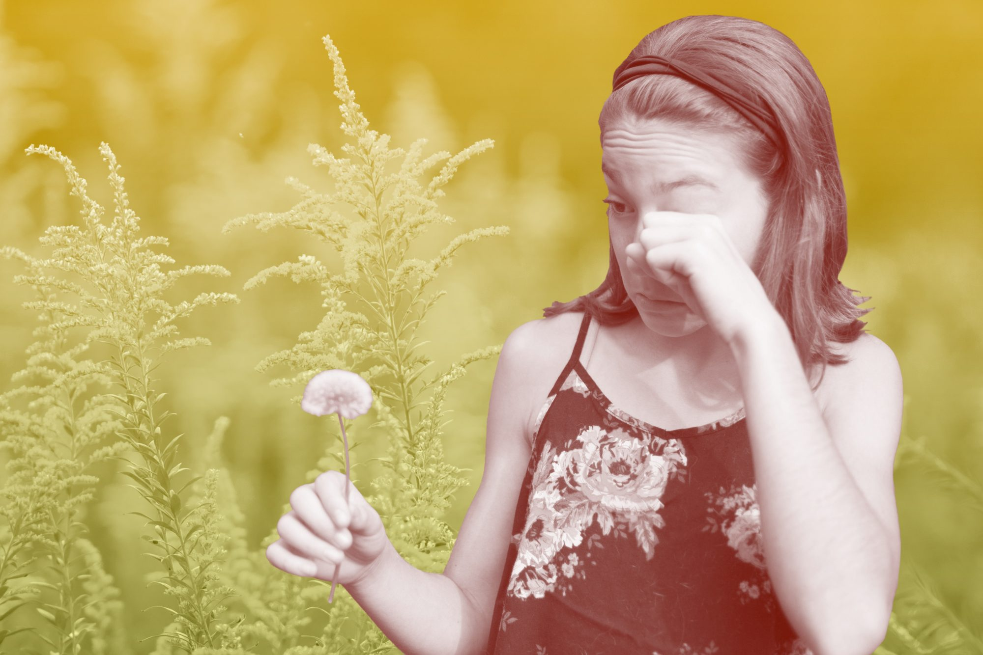 girl rubbing eyes in front of pollen