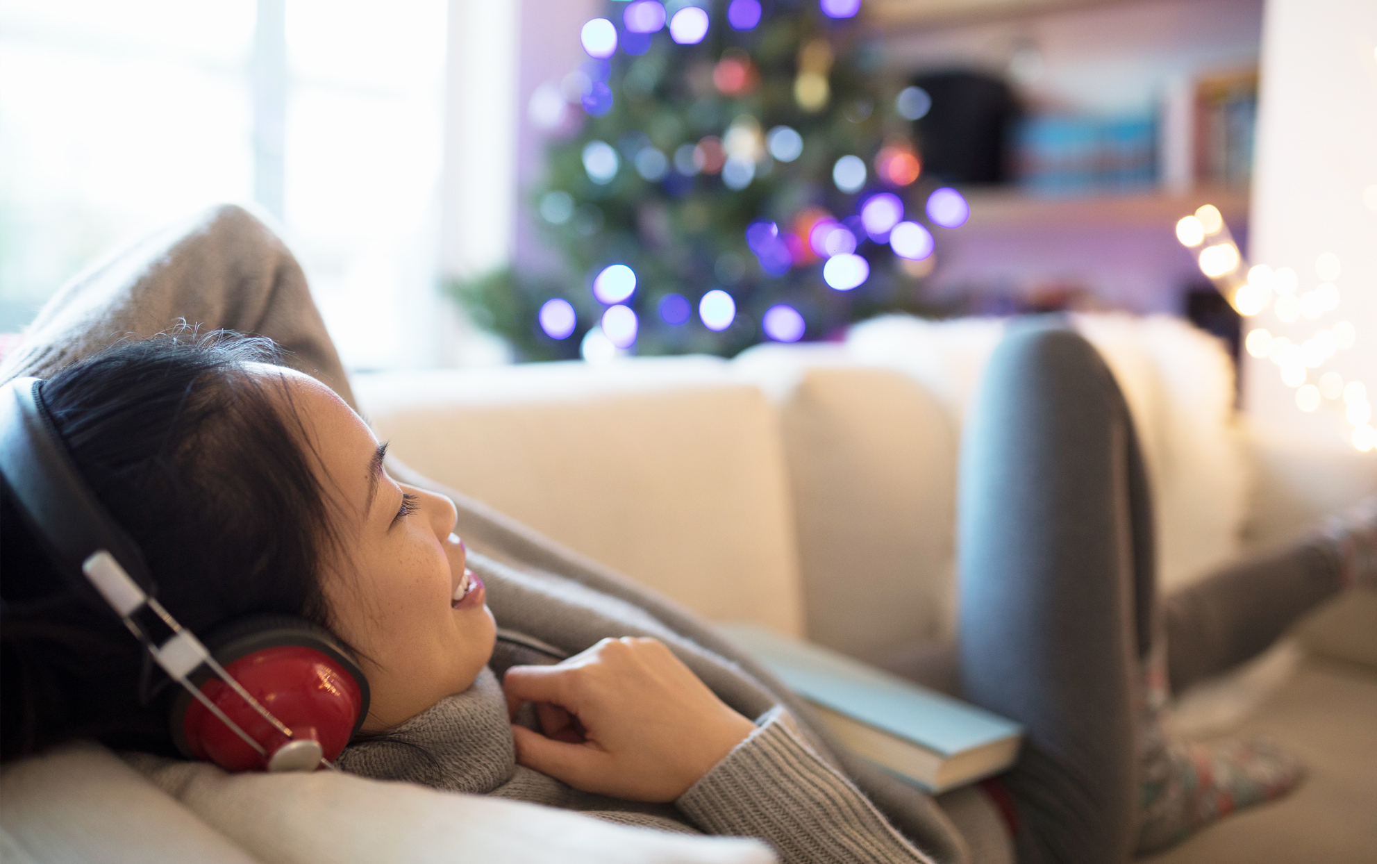 Asian Girl With Red Headphones on Couch by Christmas Tree