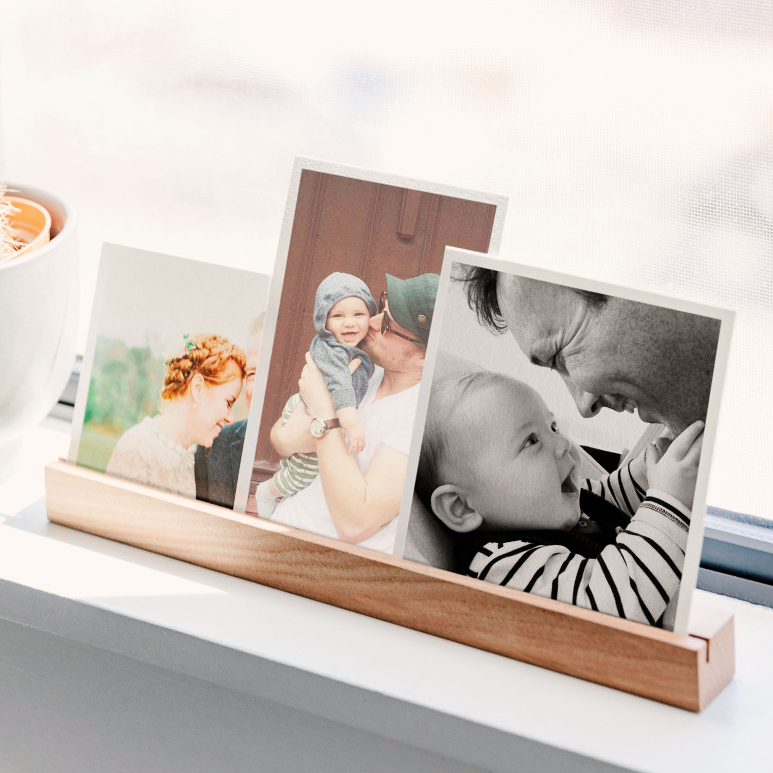 wooden photo ledge holding three family photos