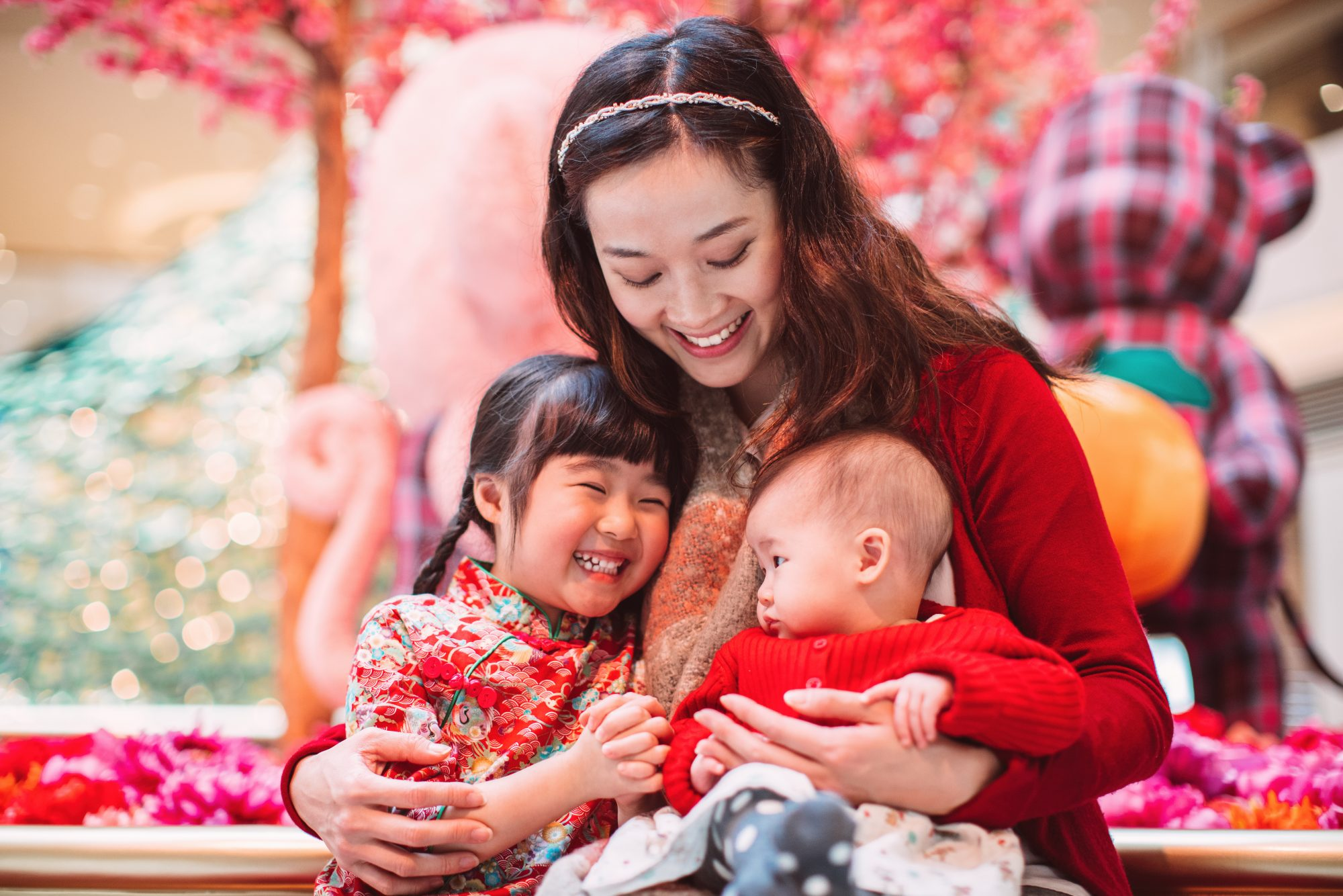 Pretty young mom hugging her little daughter and her baby joyfully during Chinese New Year.