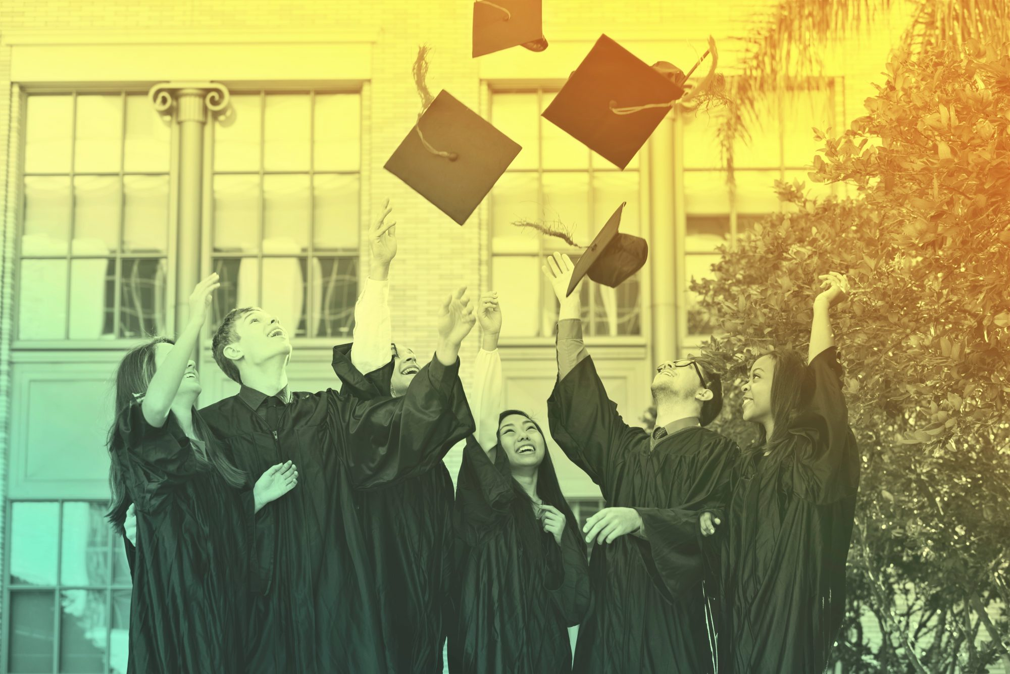 Group of students at graduation tossing caps