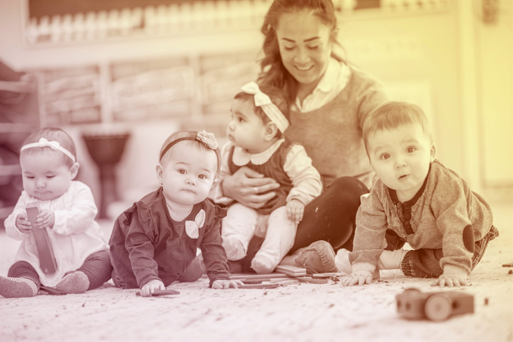 group of babies in daycare center with teacher
