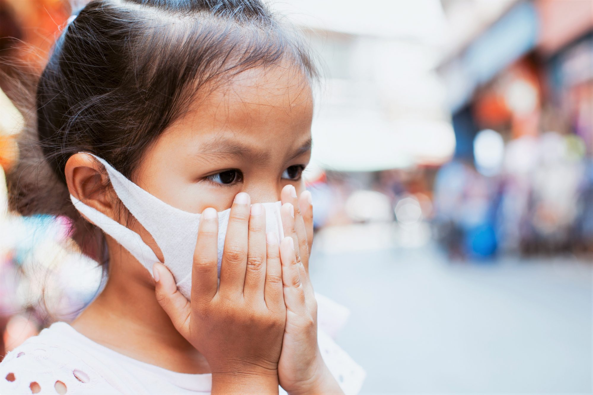Close-Up Of Asian Girl Wearing Protective Mask With Hands Covering Mouth