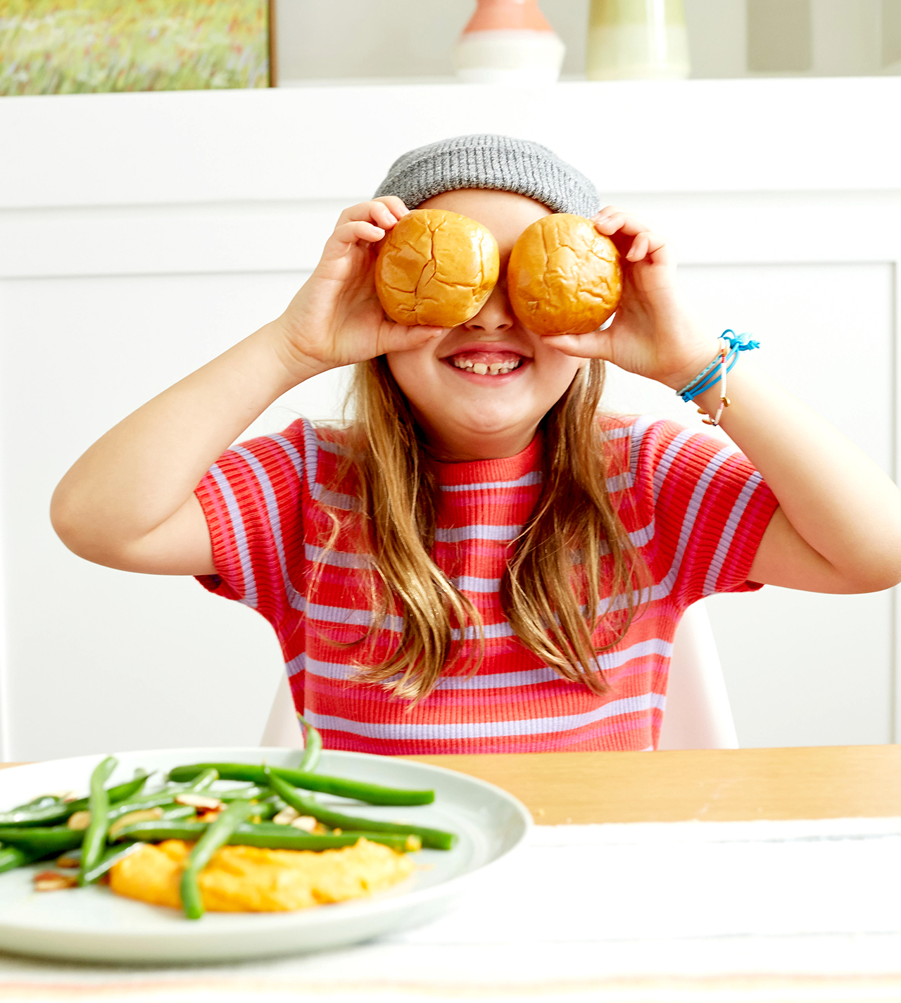Child with buns over eyes while eating dinner