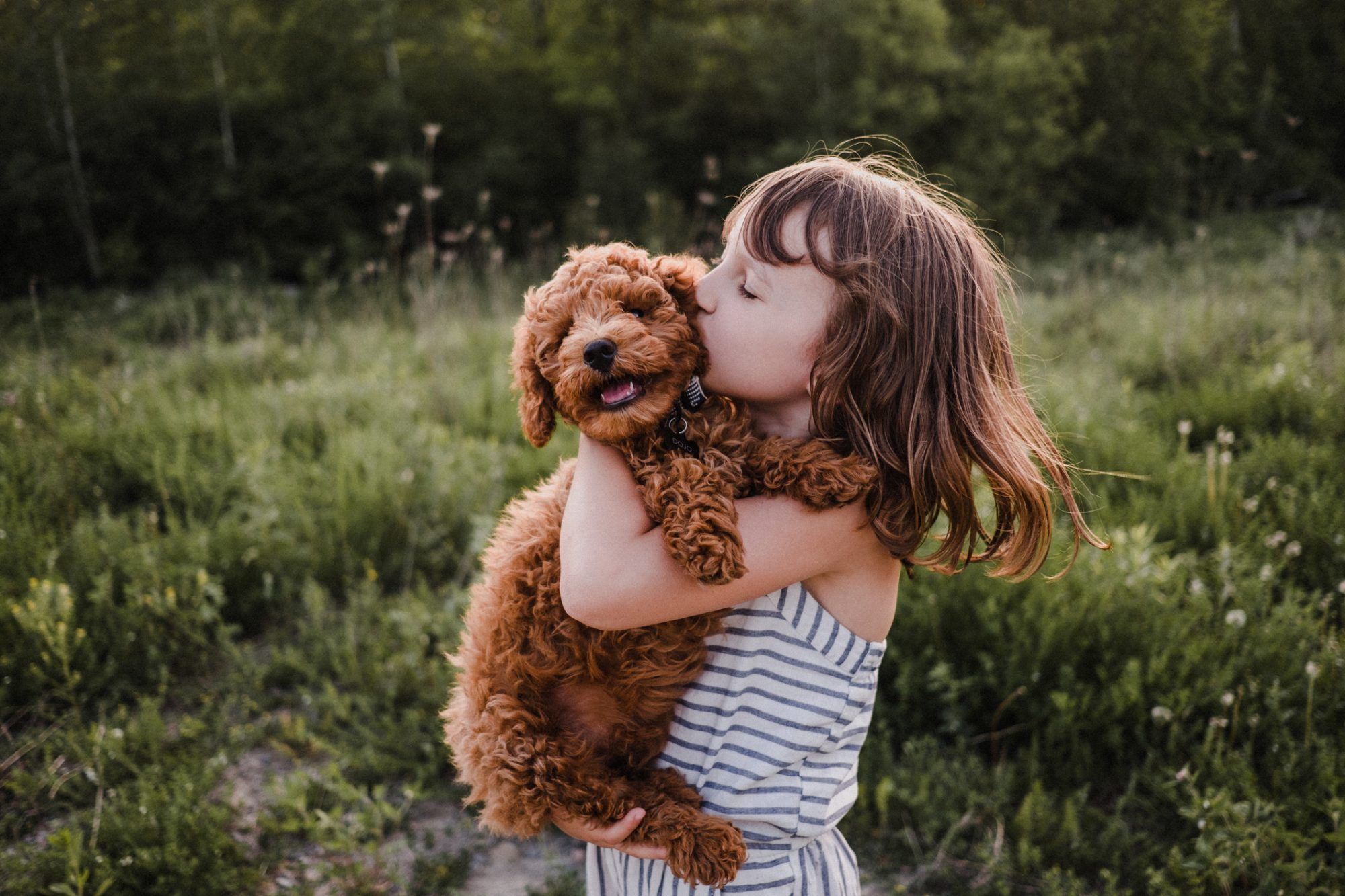 girl holding puppy kissing head outside