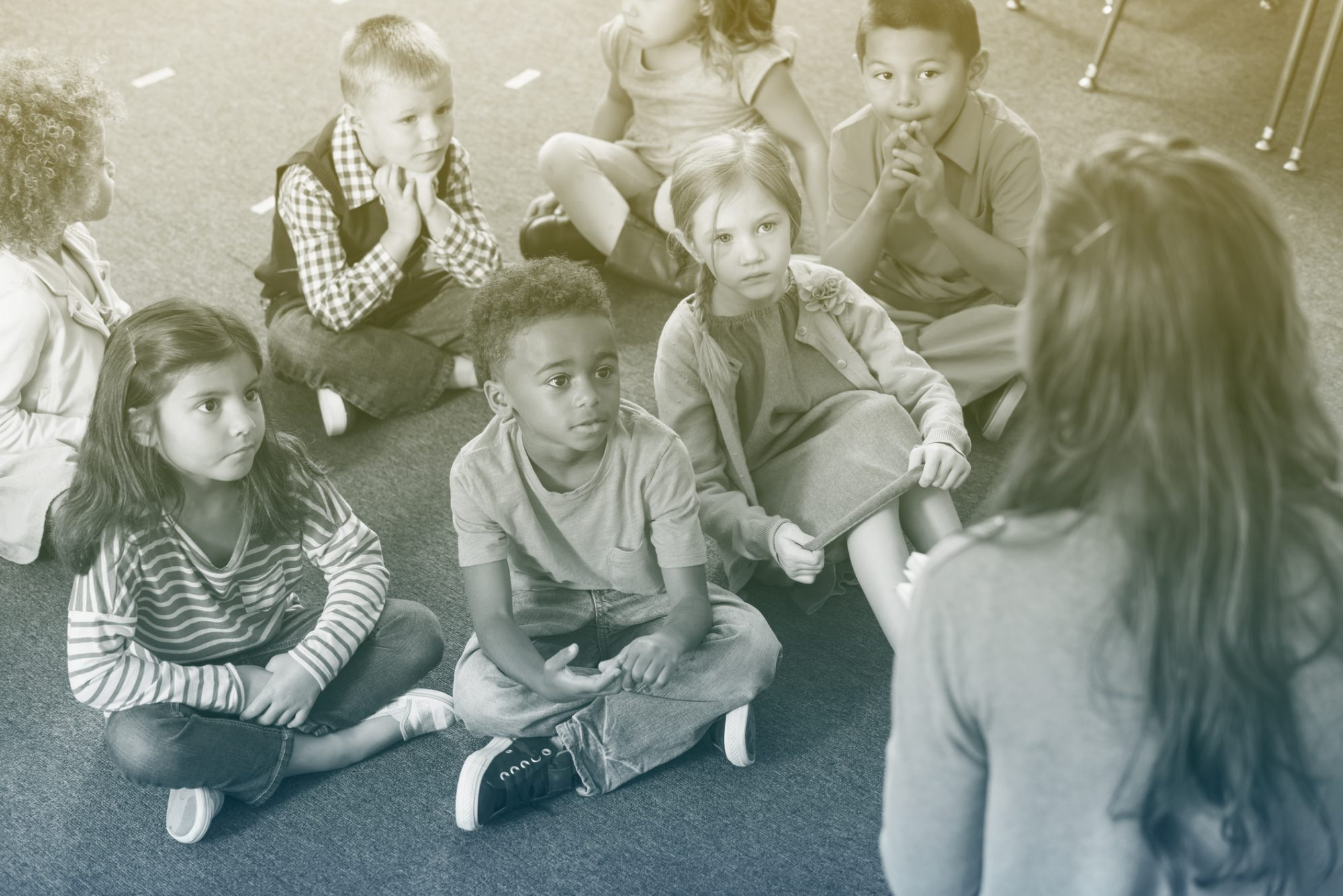 Kindergarten students sitting listening to teacher