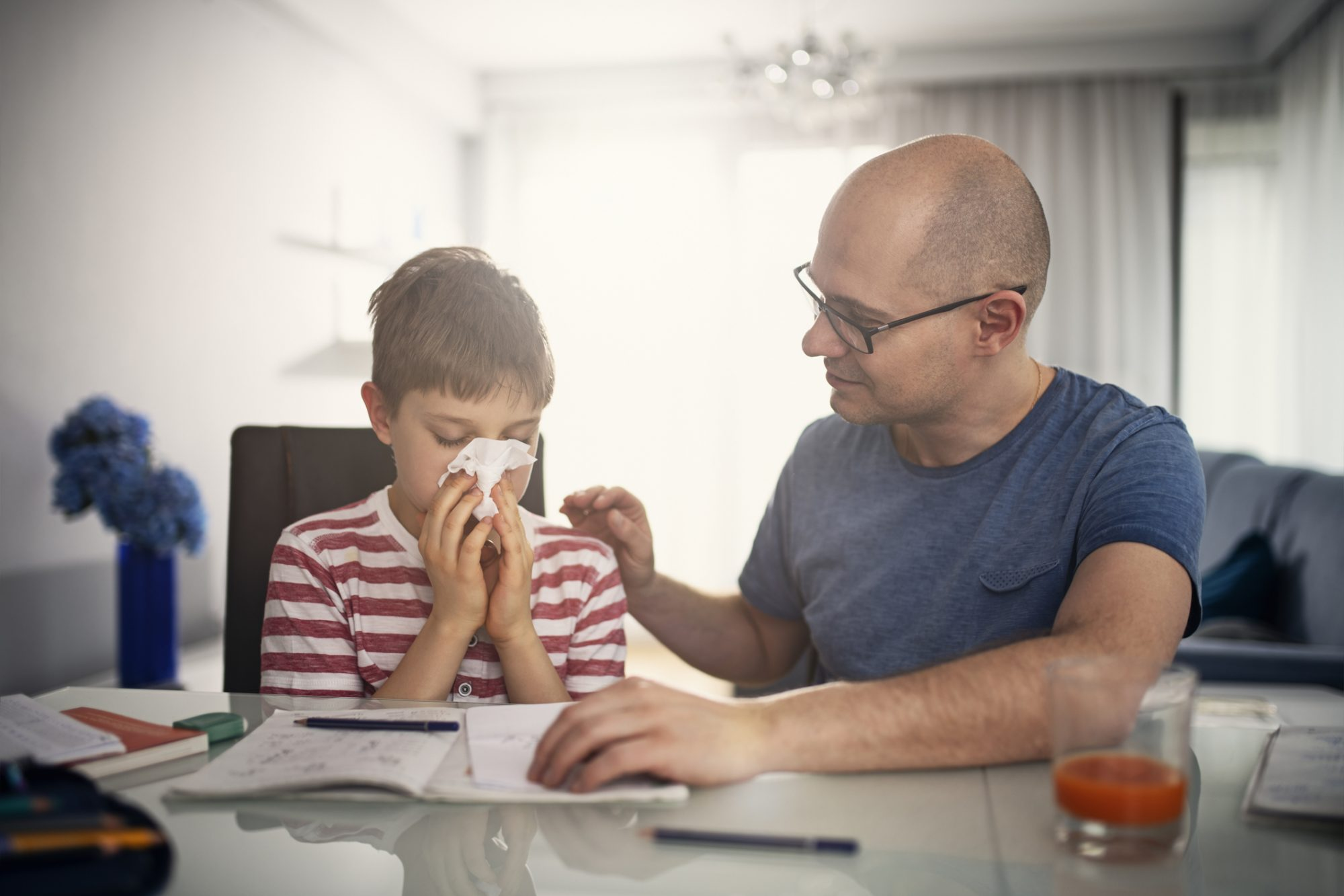 son sneezing in tissue and father sitting next to him