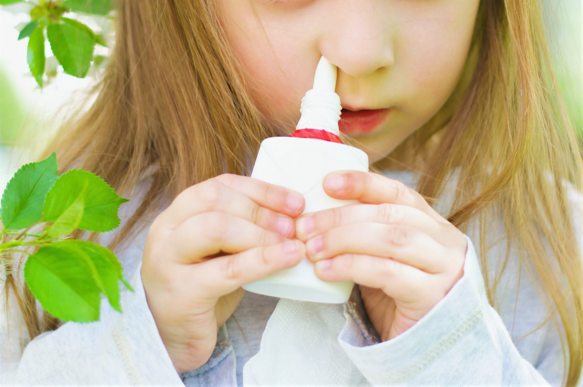 Little girl spraying nasal spray in nose