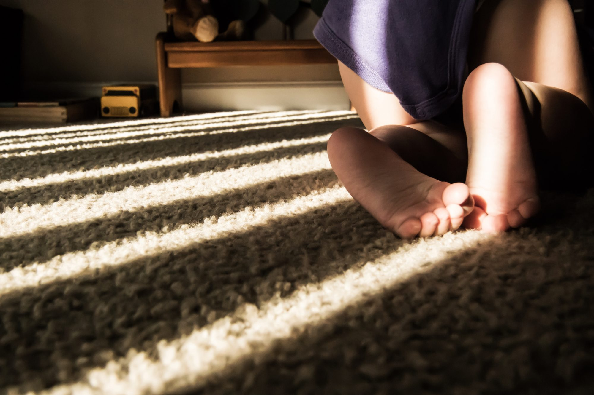 Low Section Of Toddler Crawling On Carpet At Home