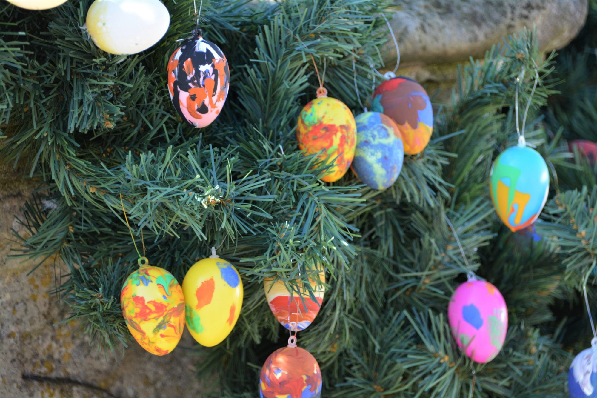 Close-Up Of Multi Colored Decorated Eggs Hanging On Christmas Tree