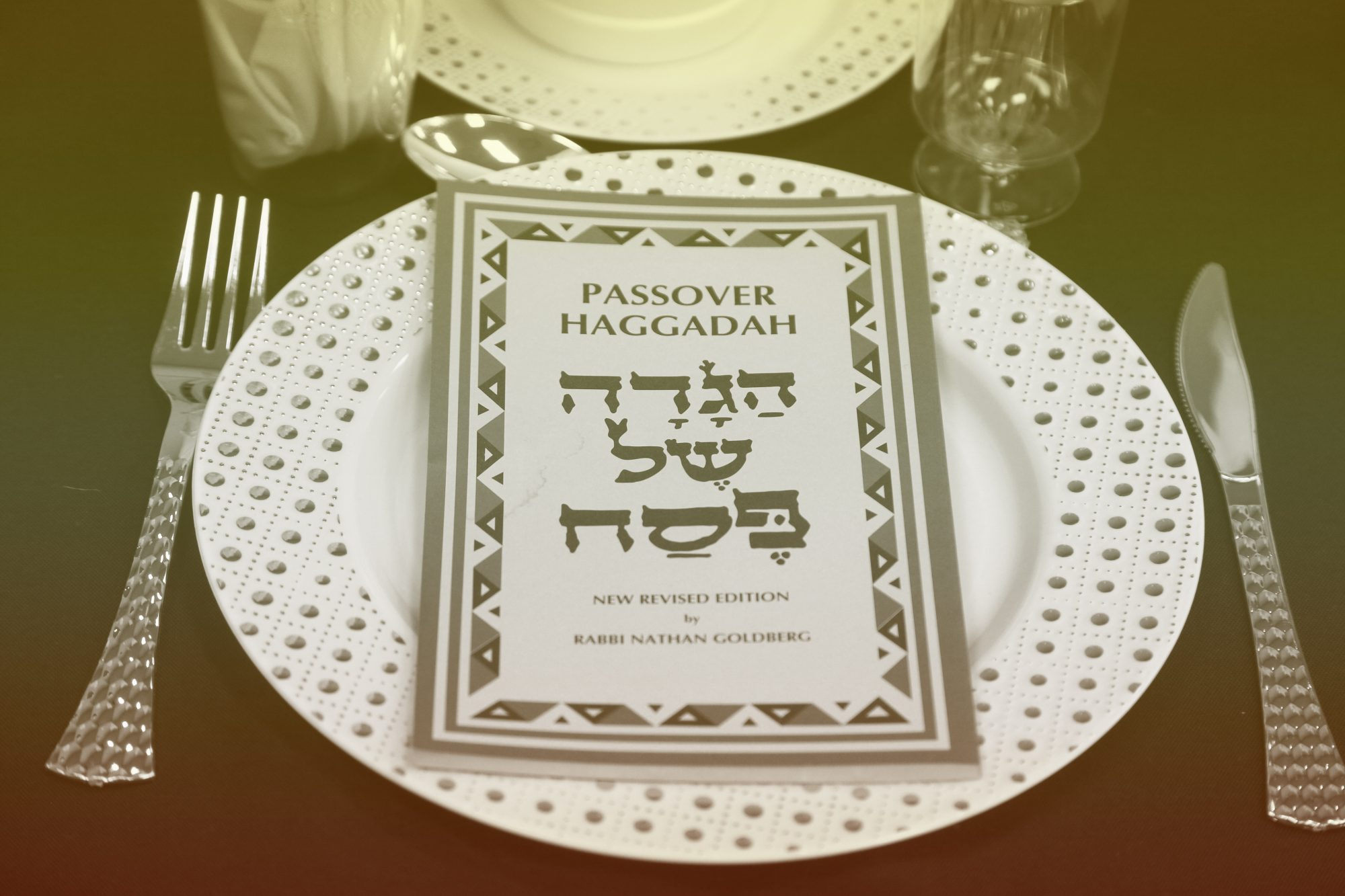 Passover Haggadah rests on a plate during a Passover seder