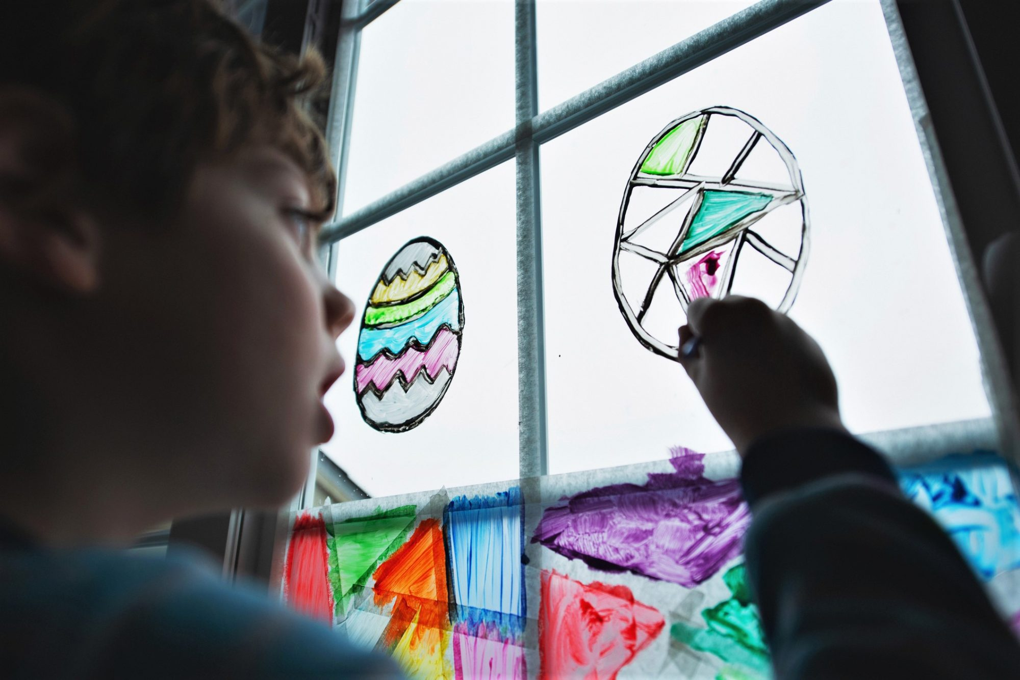Boy Paints Easter Eggs on Window