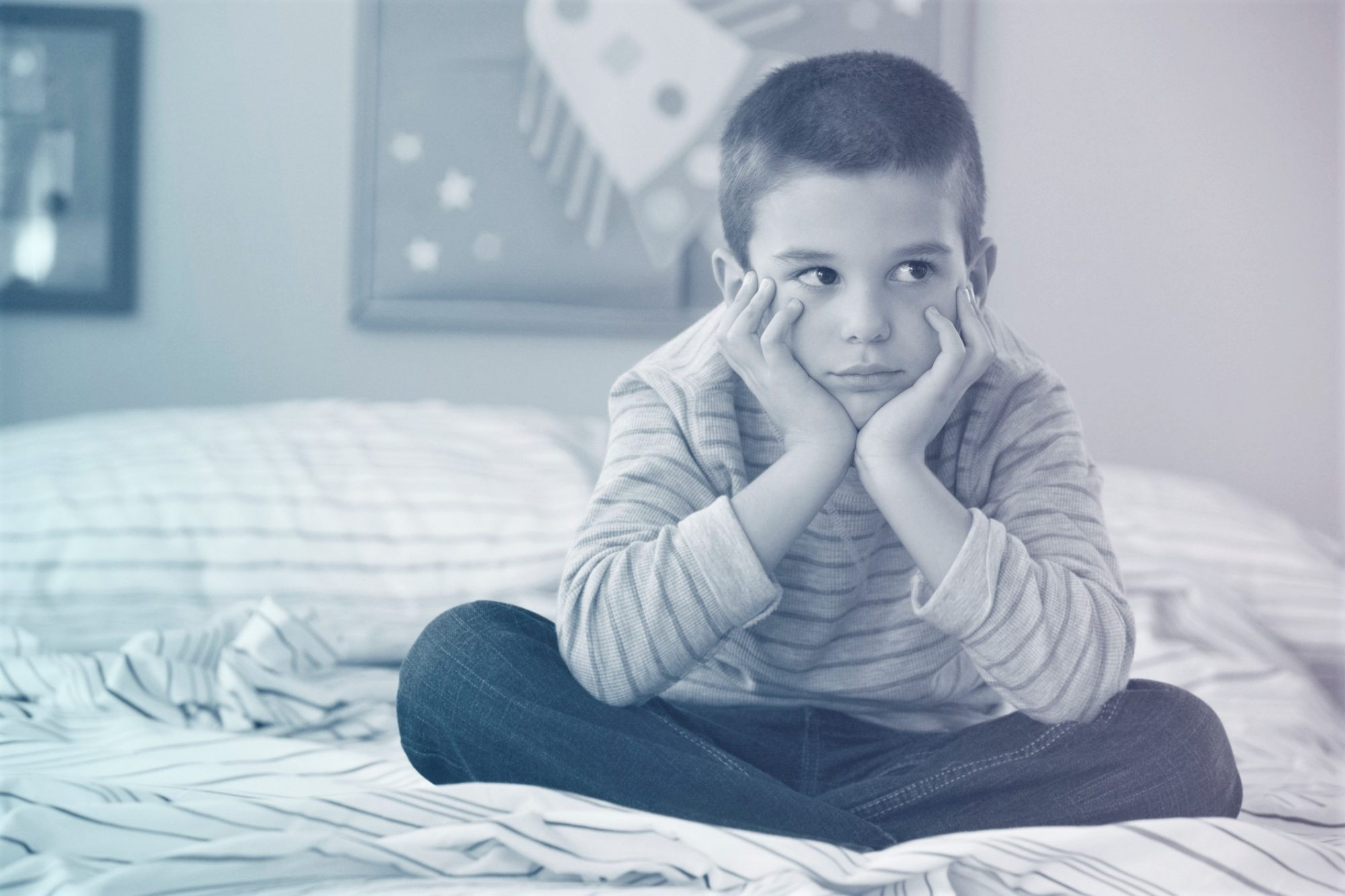 Unhappy boy sitting on bed