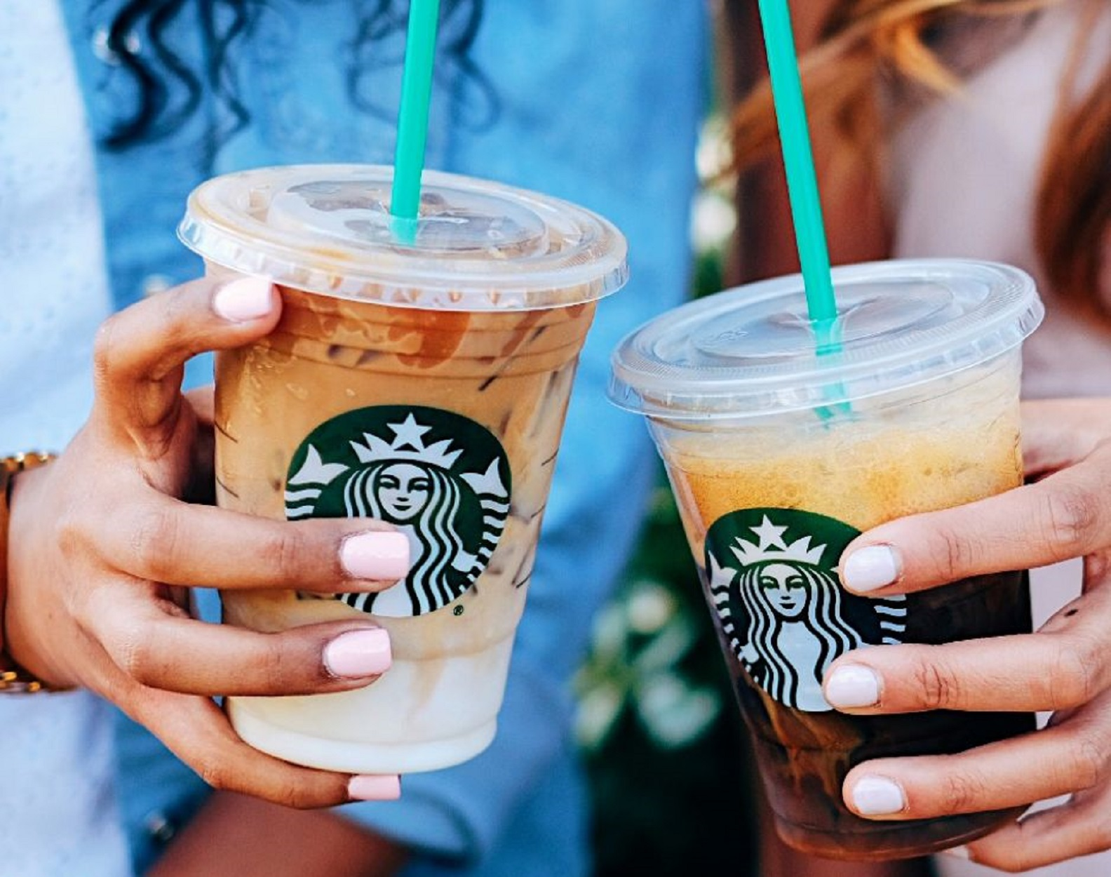 Two hands holding iced coffee from Starbucks