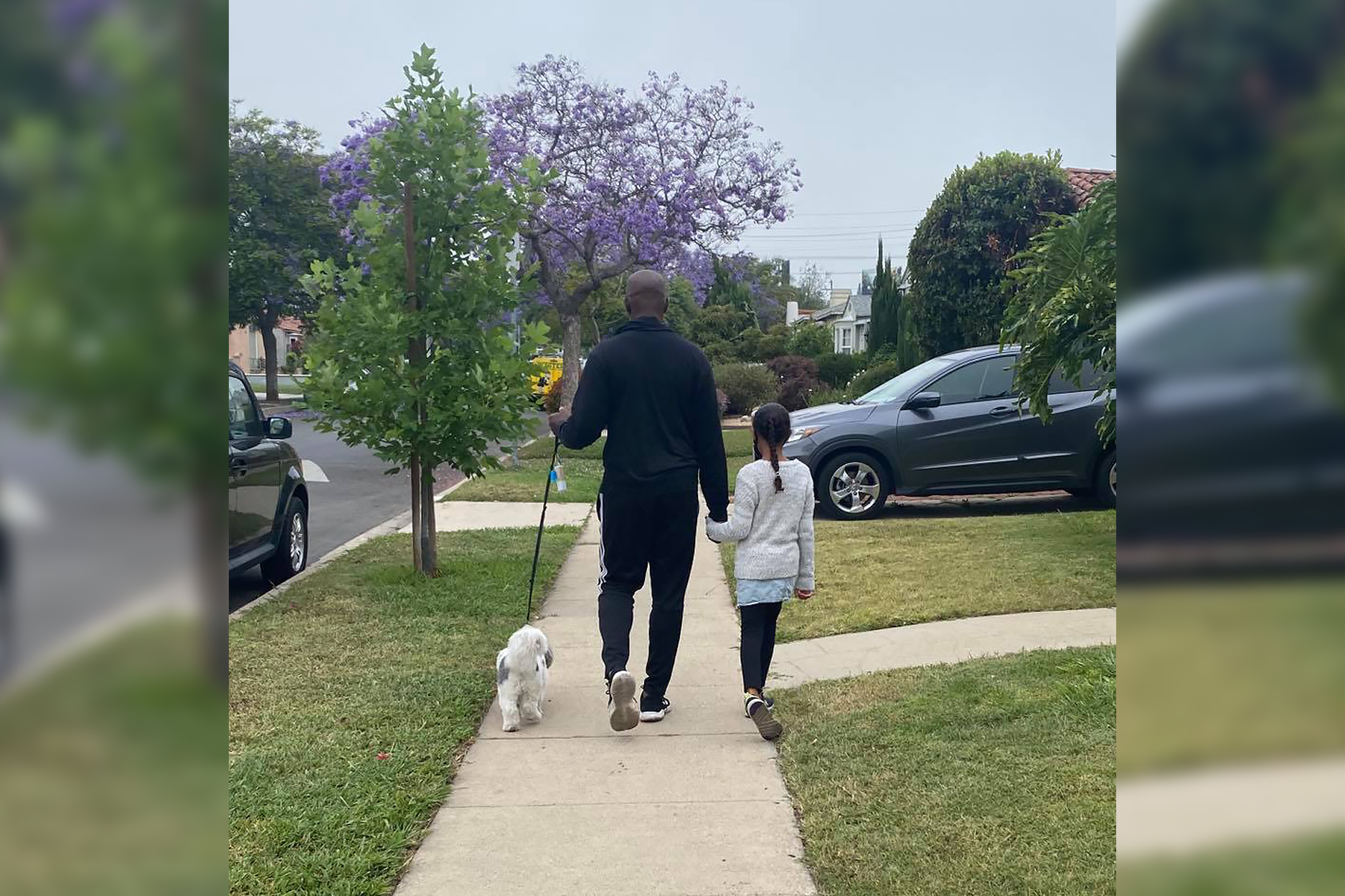 father walking with daughter and pet dog outside