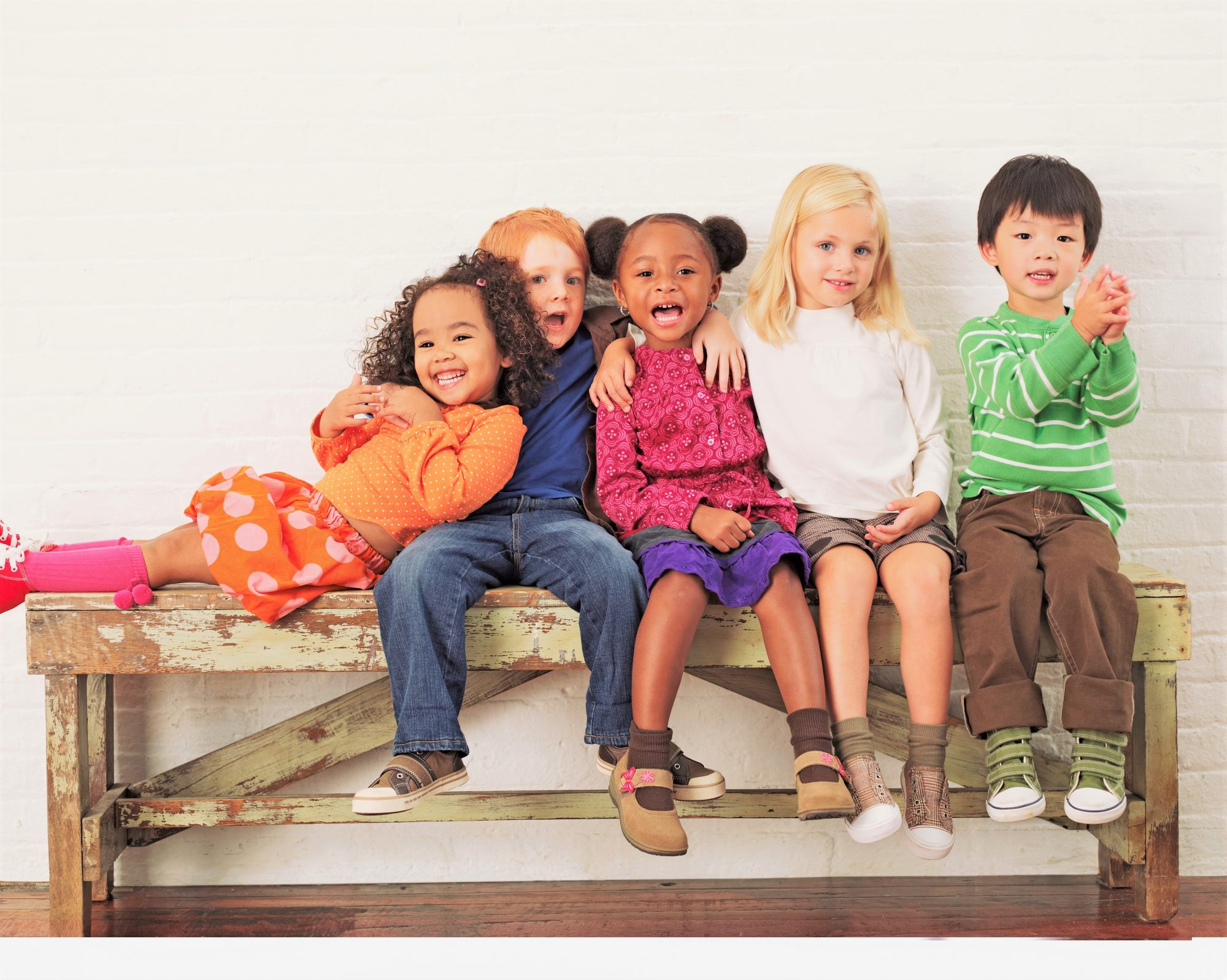 group of diverse children sitting on bench