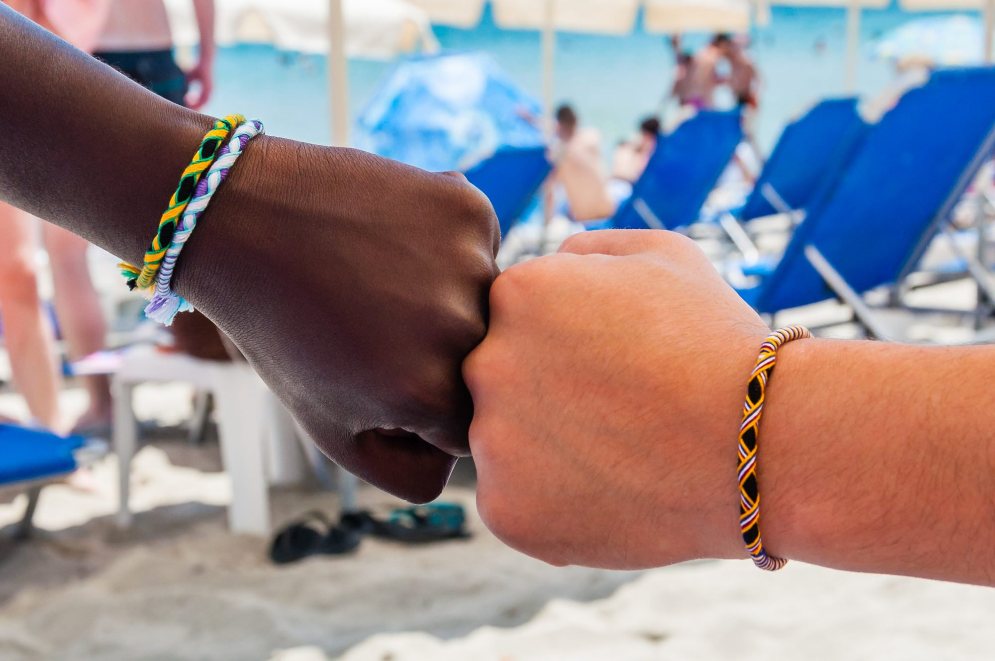 Two fists of two different ethnicity people with braided friendship bracelets