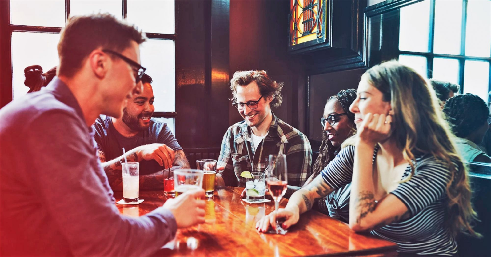 group of friends sitting at bar table with drinks