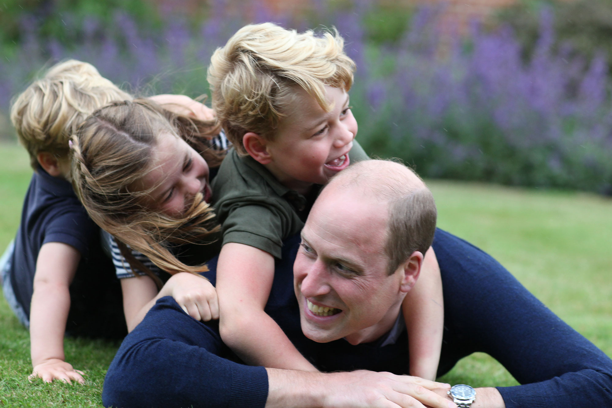 Prince William and kids laying on grass laughing