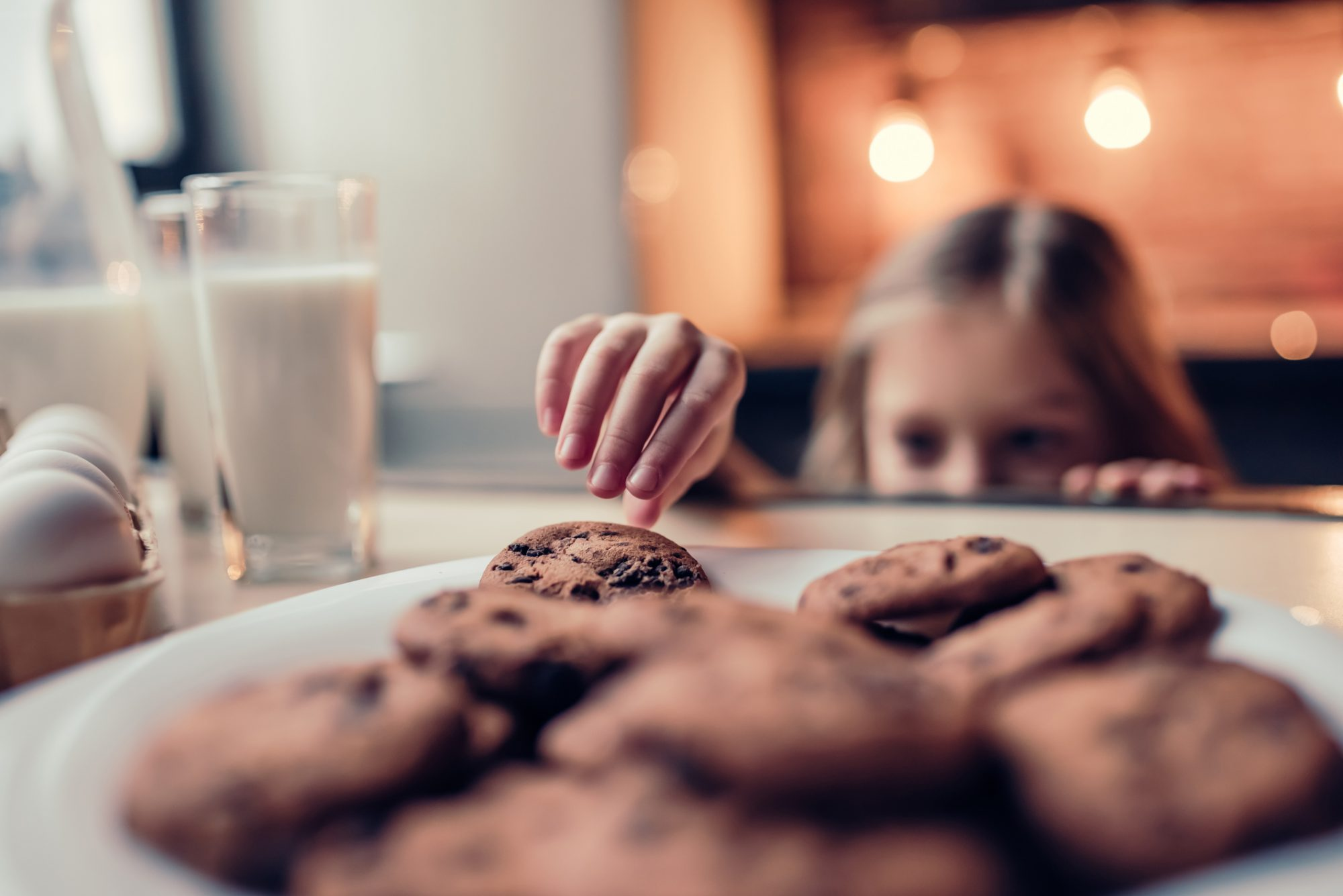 girl grabbing cookie from plate with glass of milk