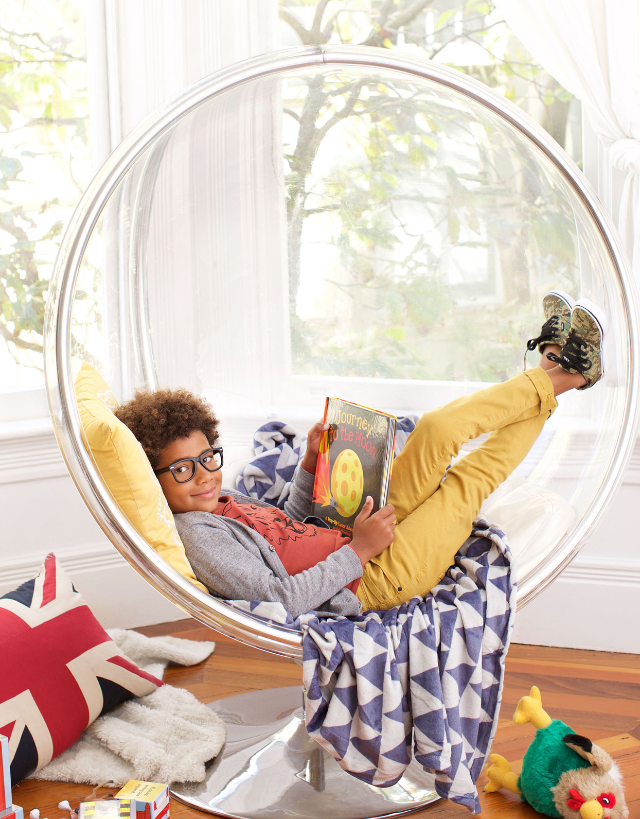 boy reading book in clear bubble chair