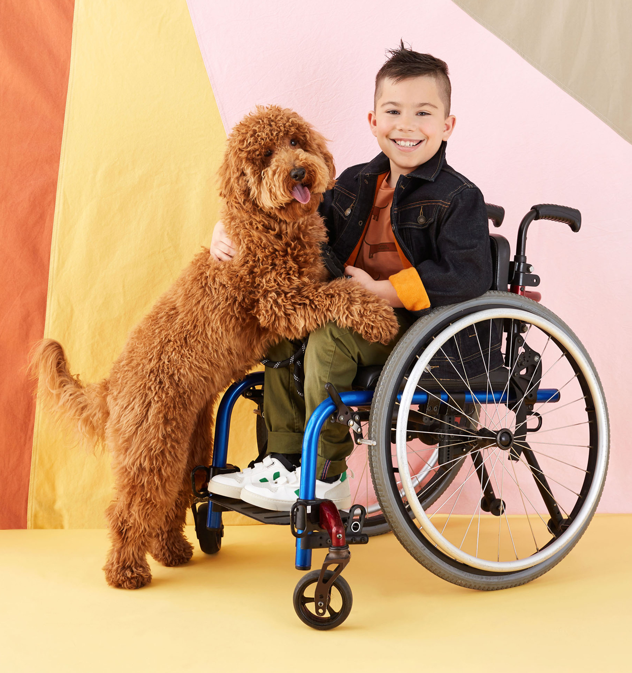 kid sitting in wheelchair smiling with dog