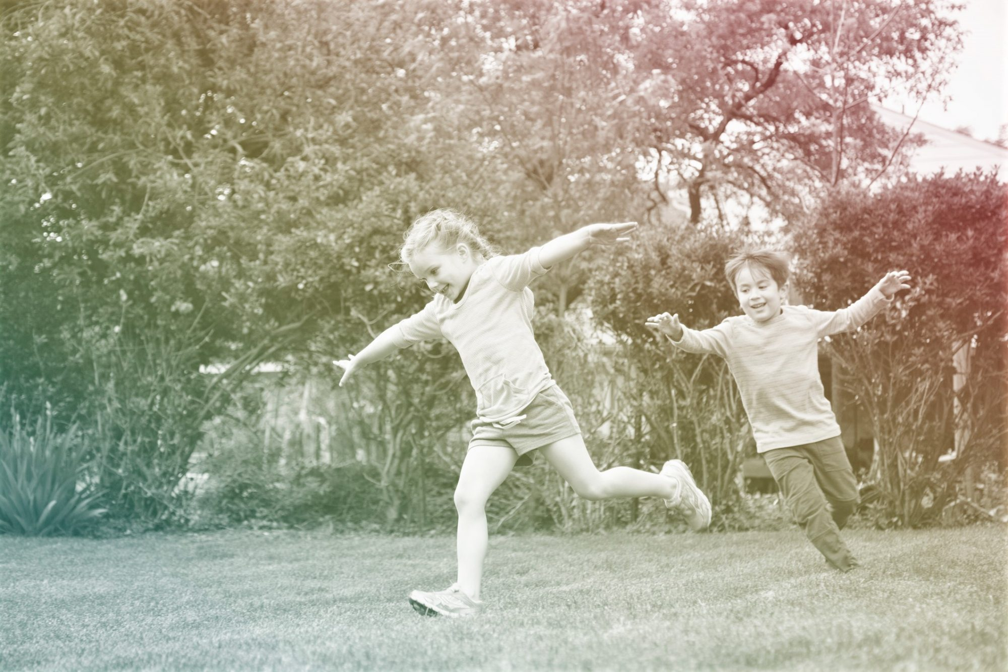 two children running around outside on grass outside with arms spread open