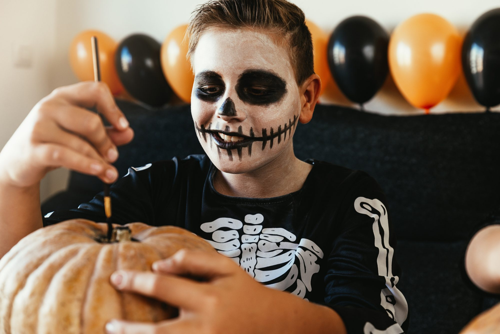 boy wearing skeleton face paint while paining a pumpkin