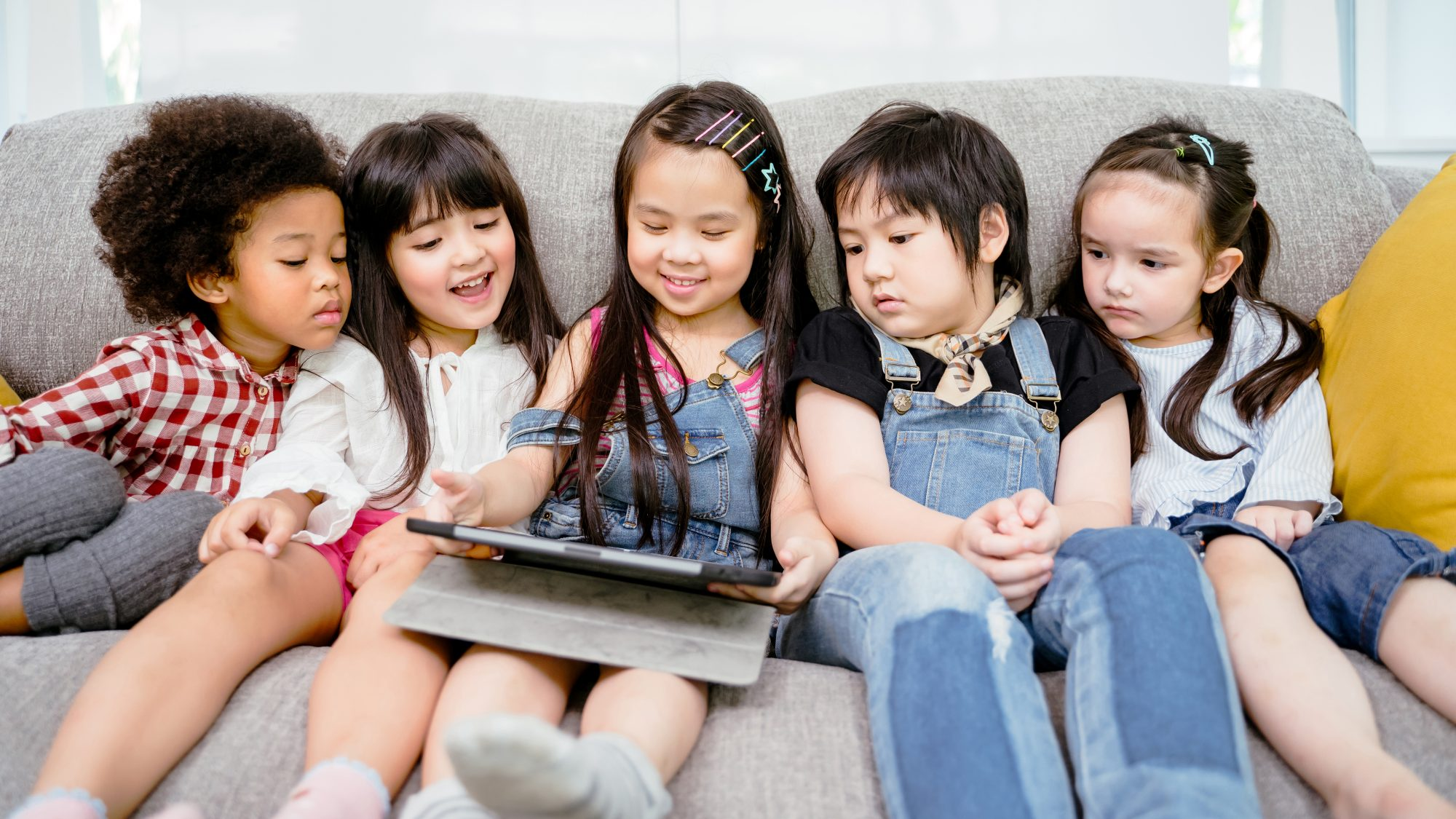 children on sofa using tablet