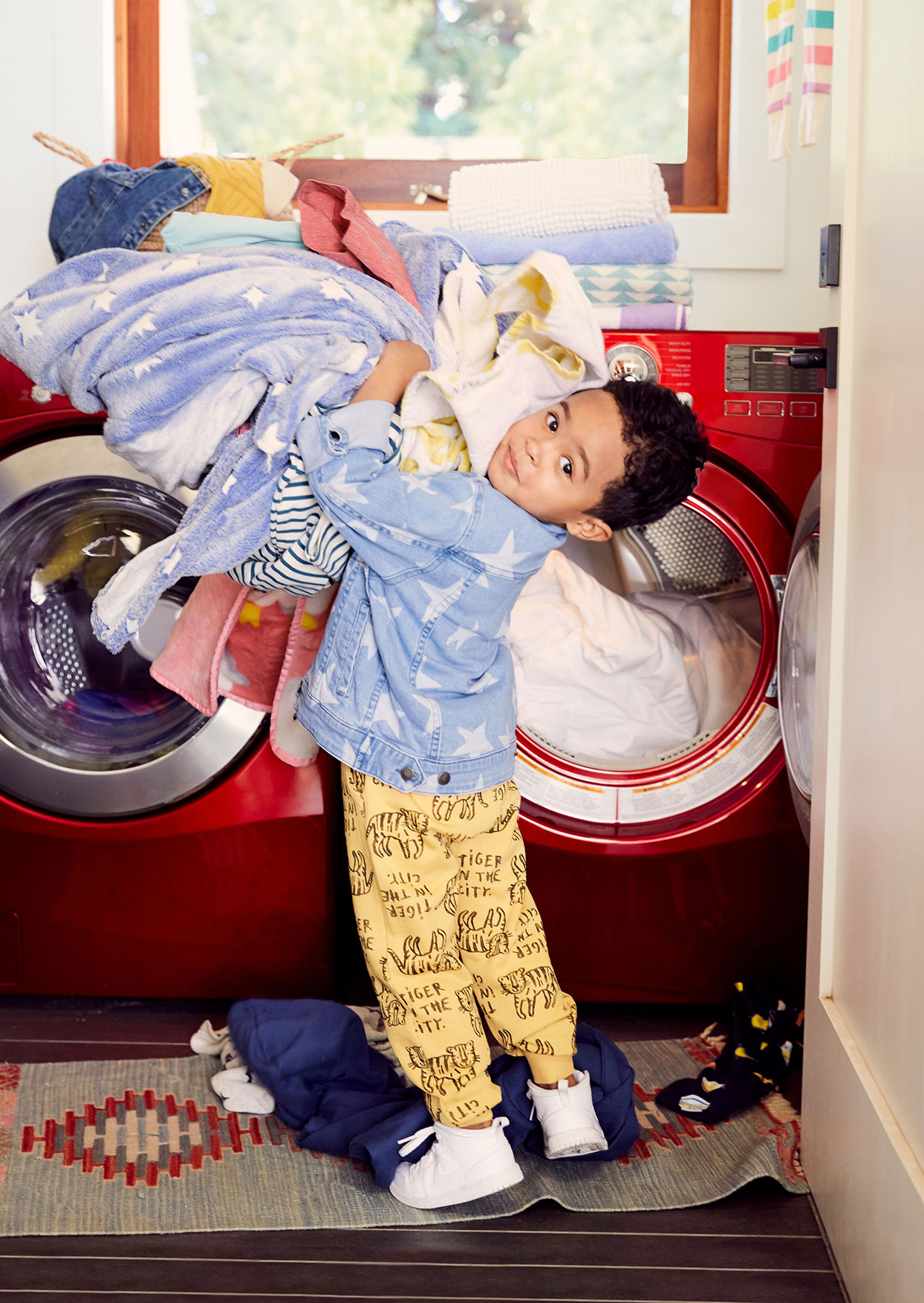 child holding pile of laundry