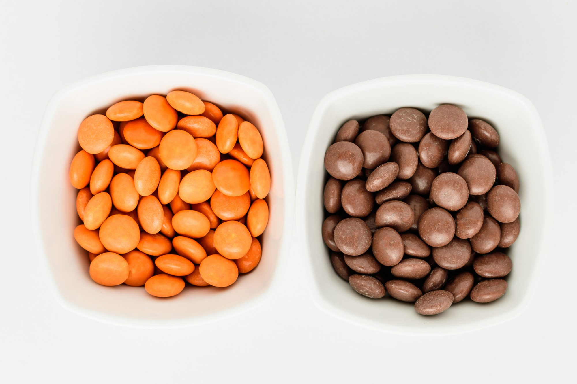 separated orange and brown m&ms in white bowls
